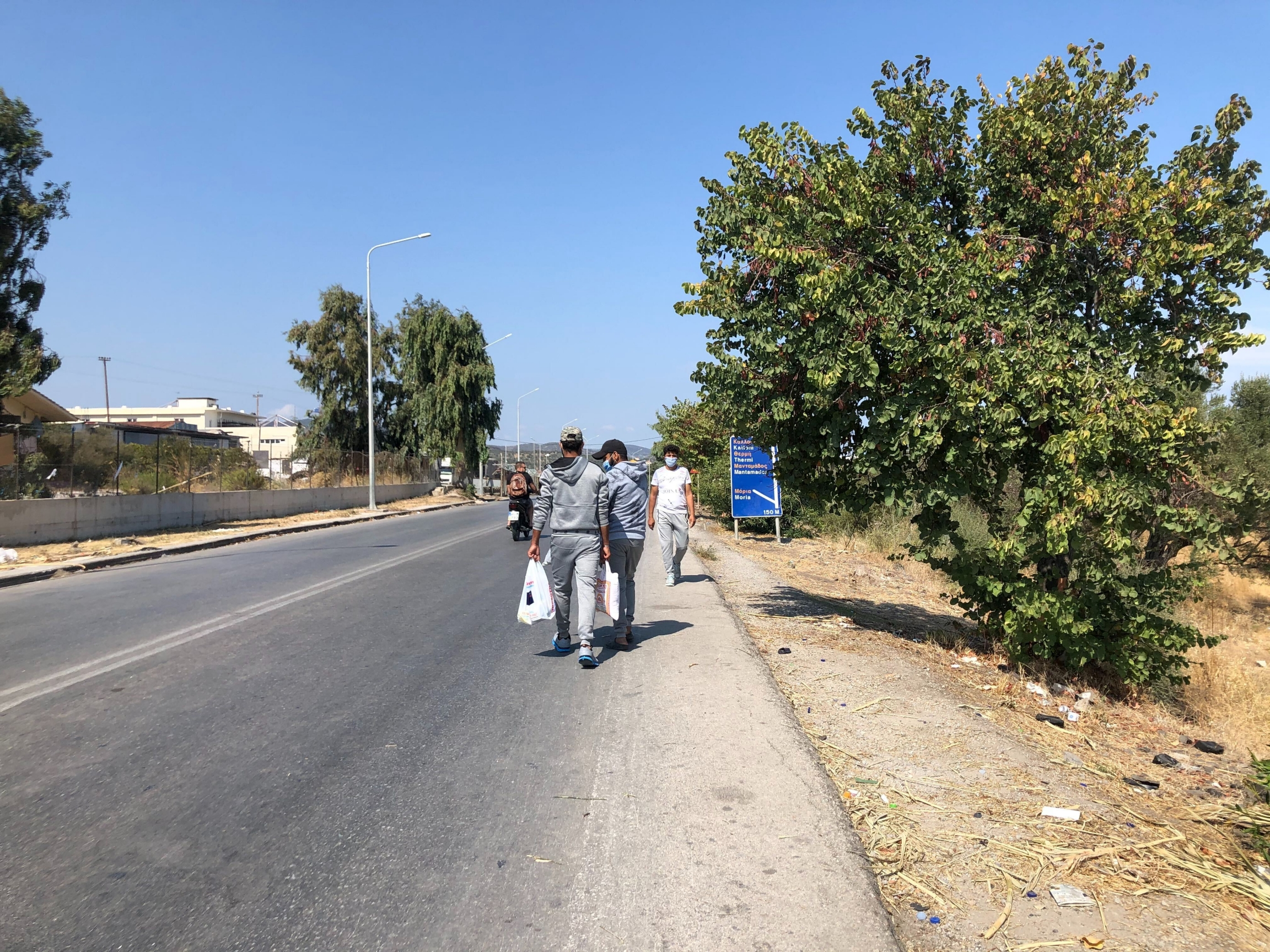 Two Syrian asylum-seekers return from a shopping trip to the port city of Mytilene, where they picked up rice, tomato sauce and other food. They say the food being distributed at the camp is not enough.