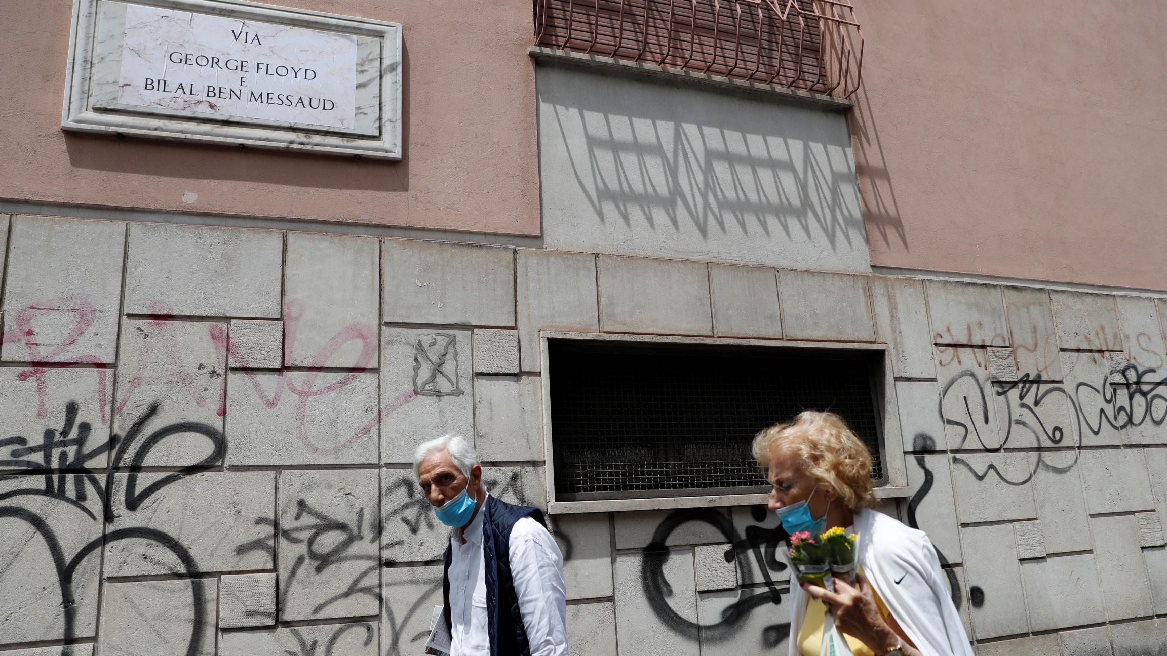 People walk near the former street sign for ''Via dell'Amba Aradam''