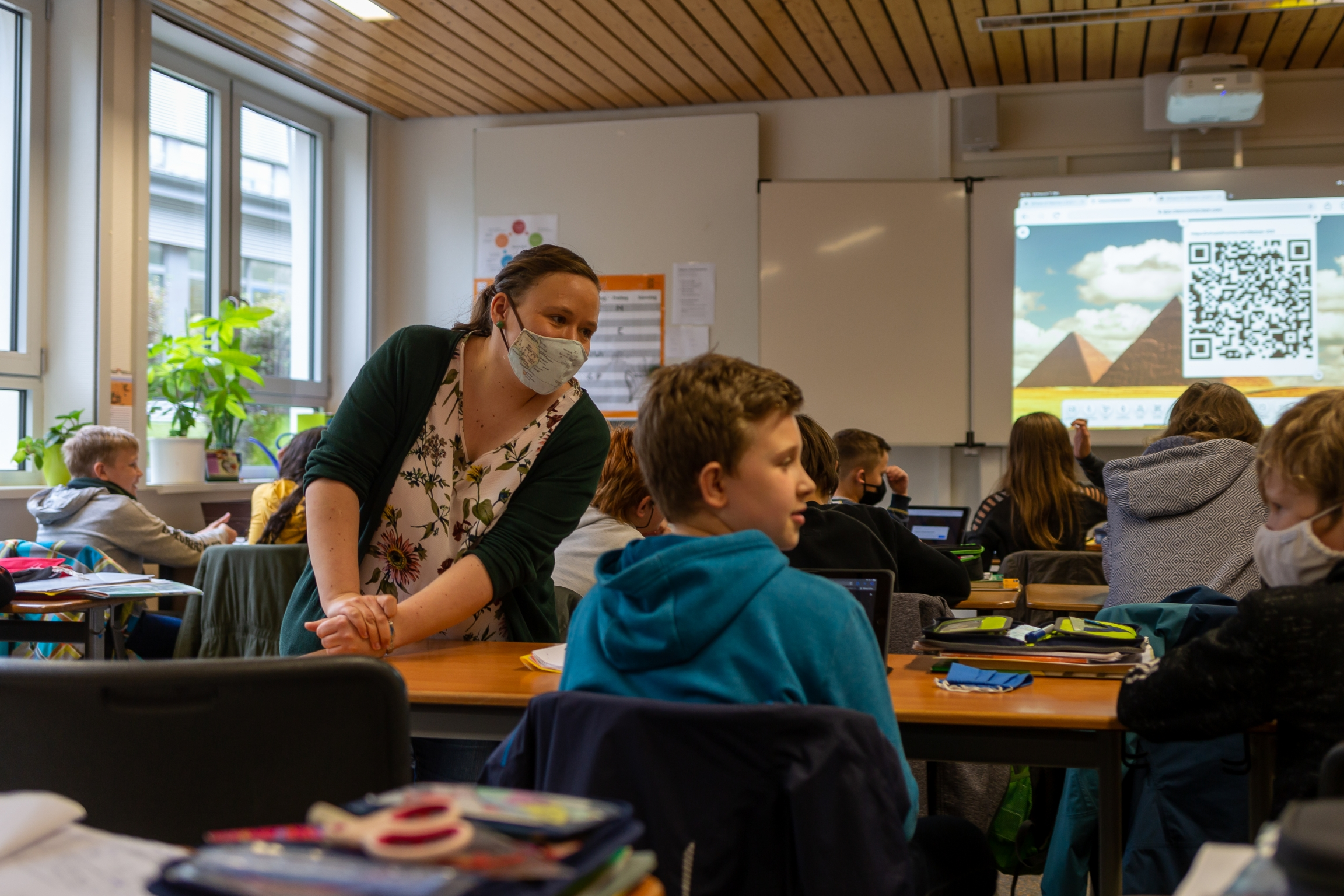 Teacher Inga Deppa works with students in an English class at Jacobishule in Kalletal, Germany. Masks were optional for students when they were seated at their desks but the regional health authority has since tighten mask rules for older students.
