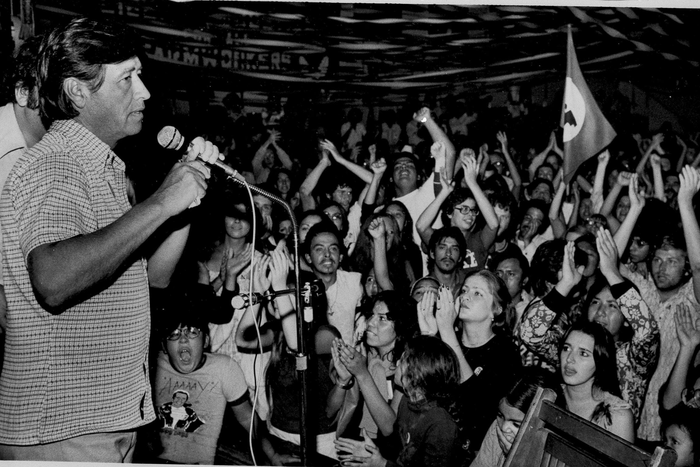 Una fotografia de Cesar Chavez hablando en frente a un grupo de personas.