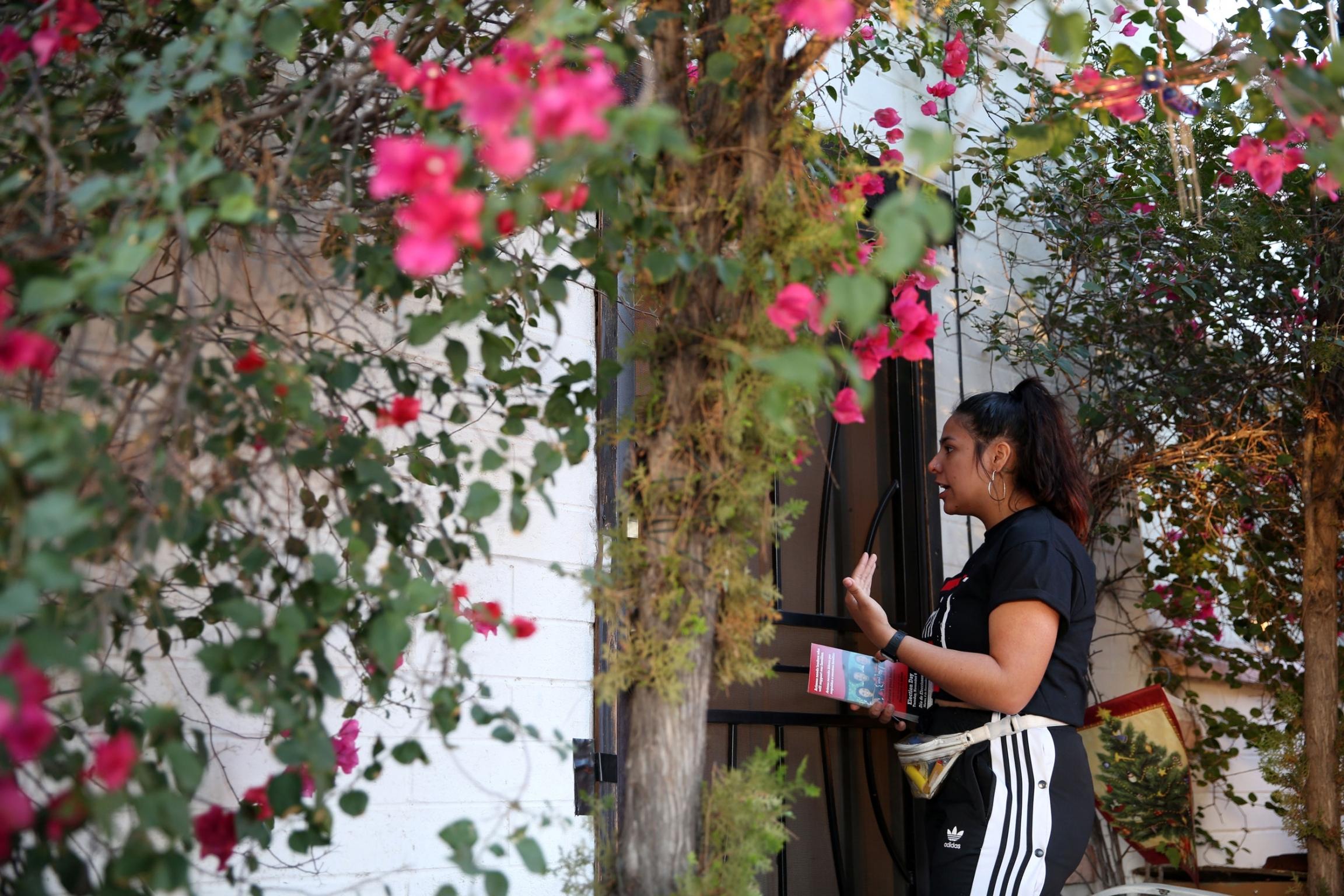 Una mujer habla con una persona que esta dentro de una casa rodeada por un jardin.