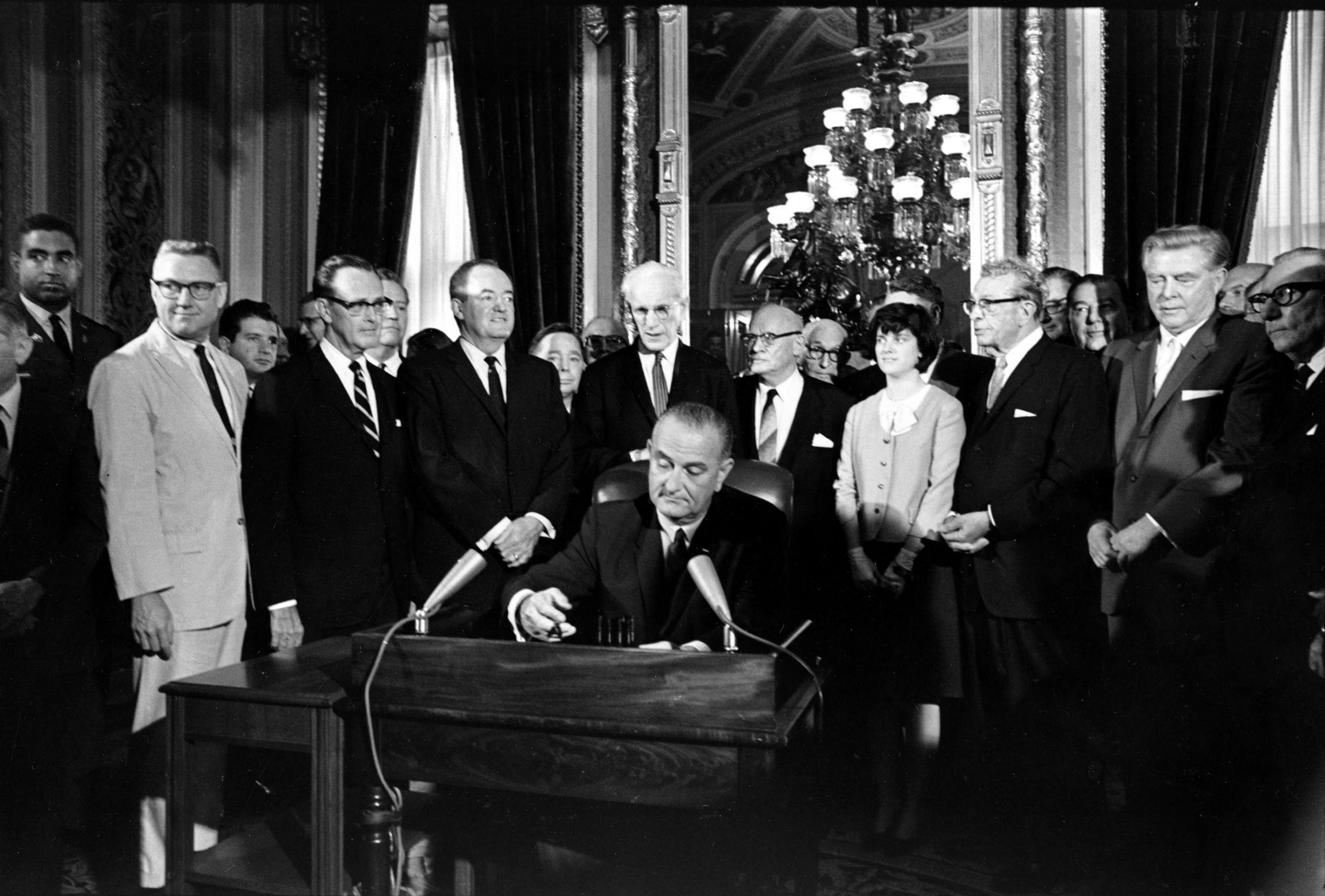 El Presidente Lyndon Johnson sentado en una mesa firmando un documento, aparece rodeado de personas.