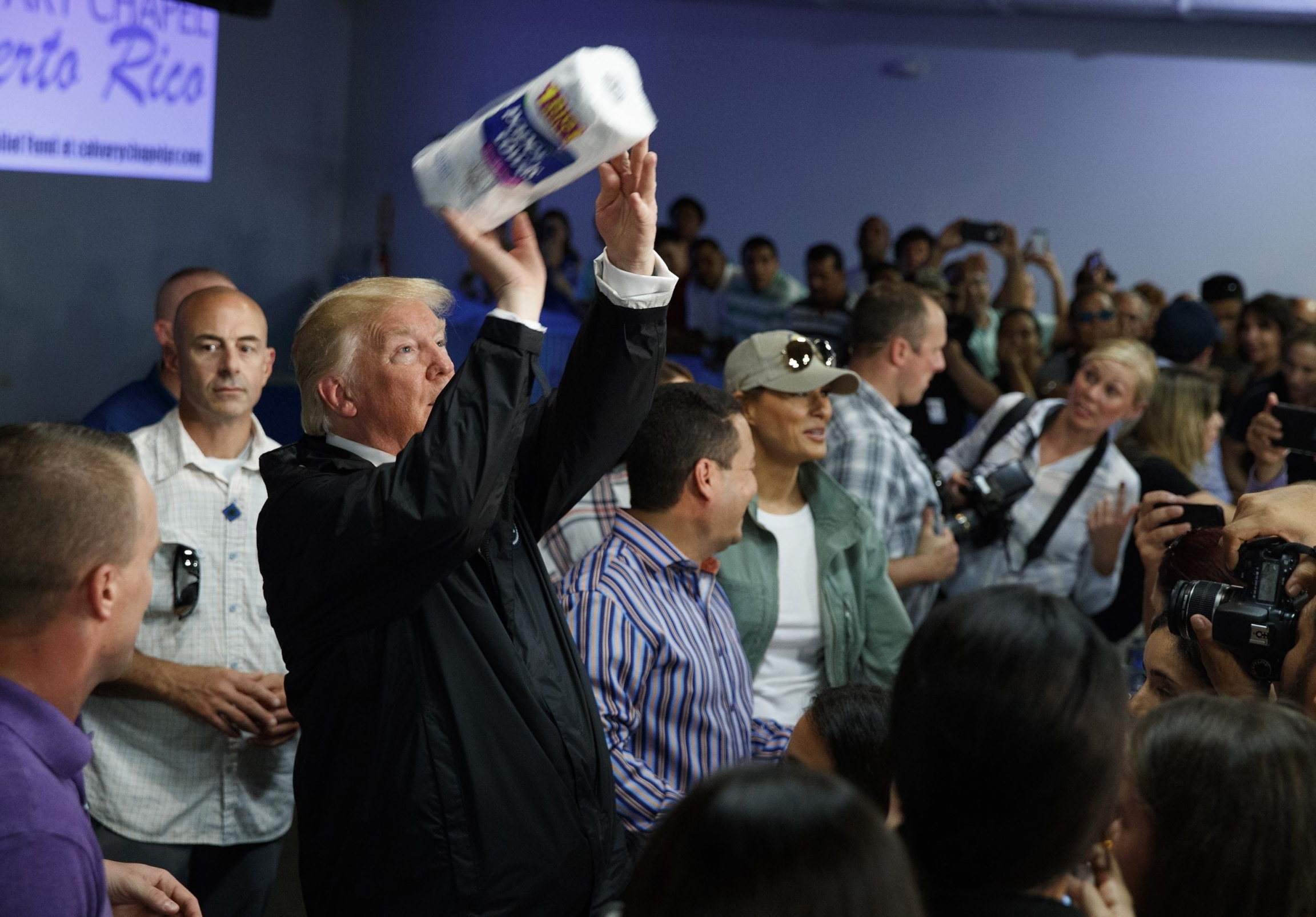 A man wearing a black suit throws a roll of paper towels to people in front of him to catch.