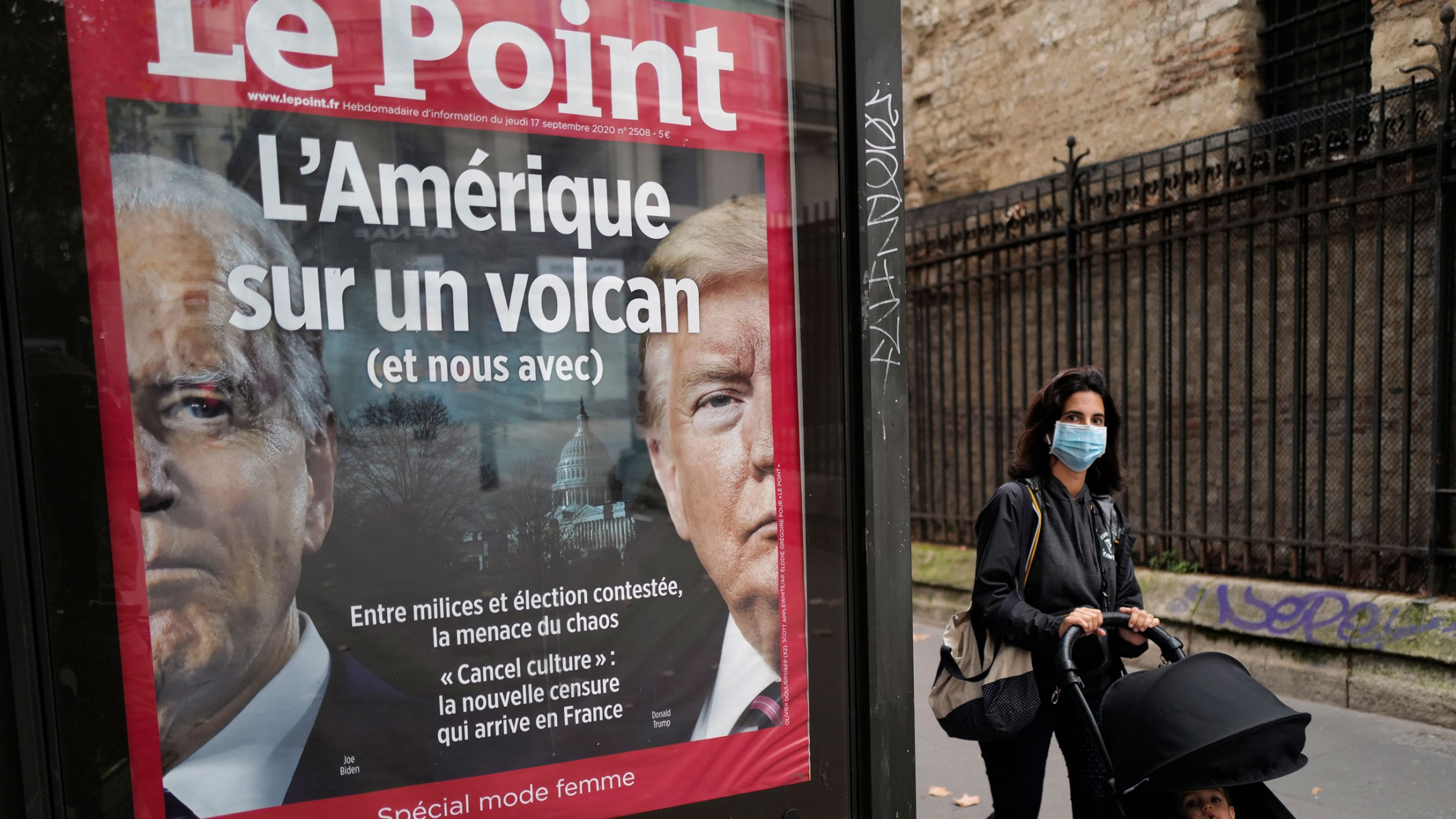 A small billboard for the French publication, Le Point, is show with the faces of Donald Trump and Joe Biden on it and a woman is shown walking past.