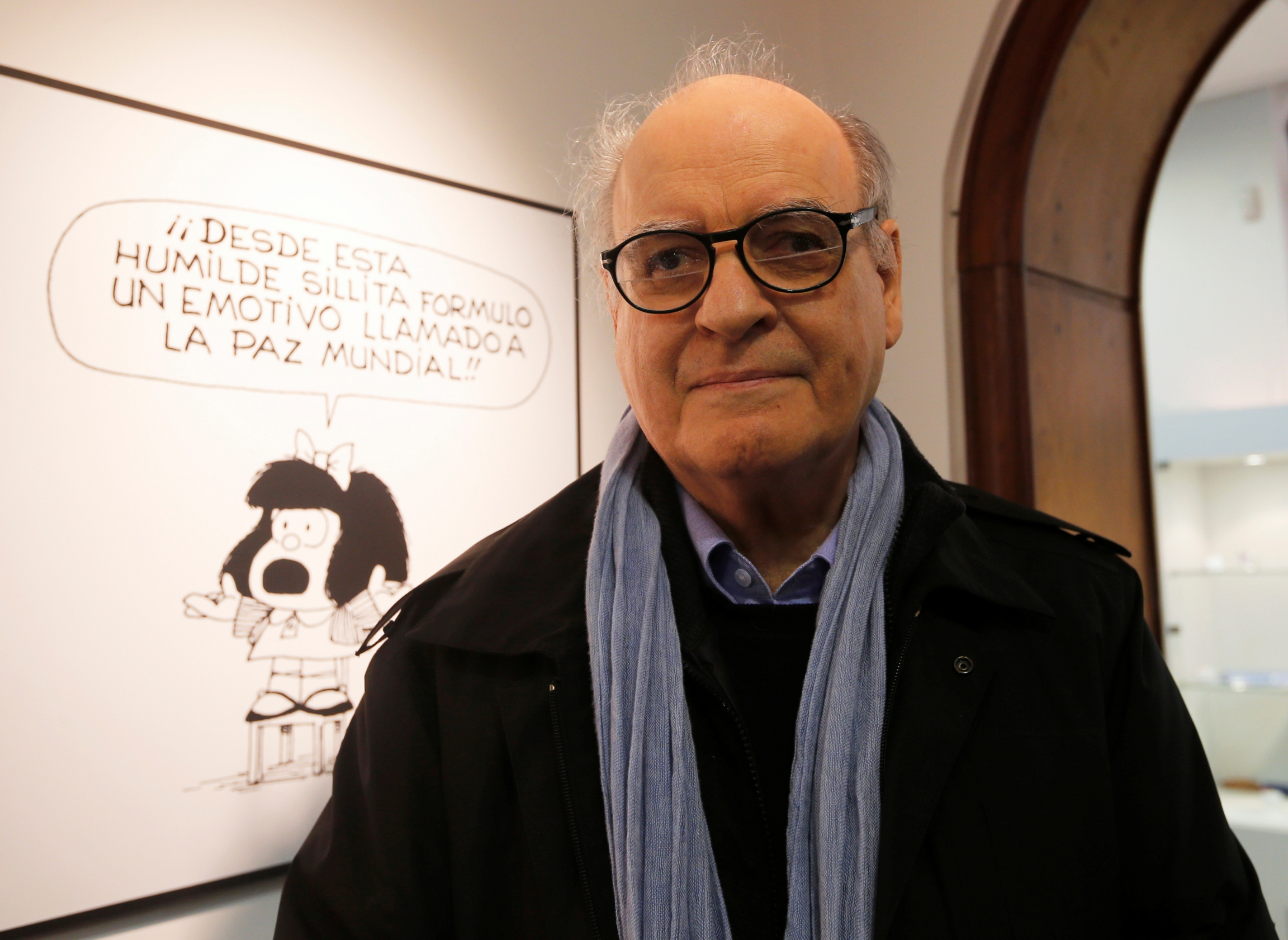 Argentine cartoonist Joaquín Salvador Lavado, also known by his pen name Quino, poses in front of an image of his most famous comic character Mafalda during the opening ceremony of the exhibition of his works at the Museo del Humor in Buenos Aires, June 1