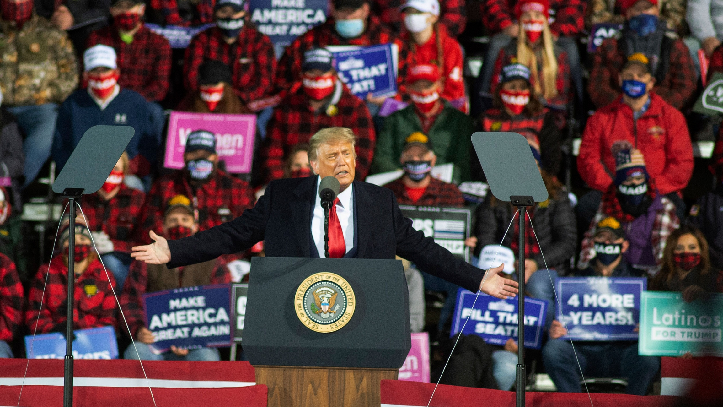 US President Donald Trump is shown with his arms outstretched, speaking at a podium with a crowd of people behind him.