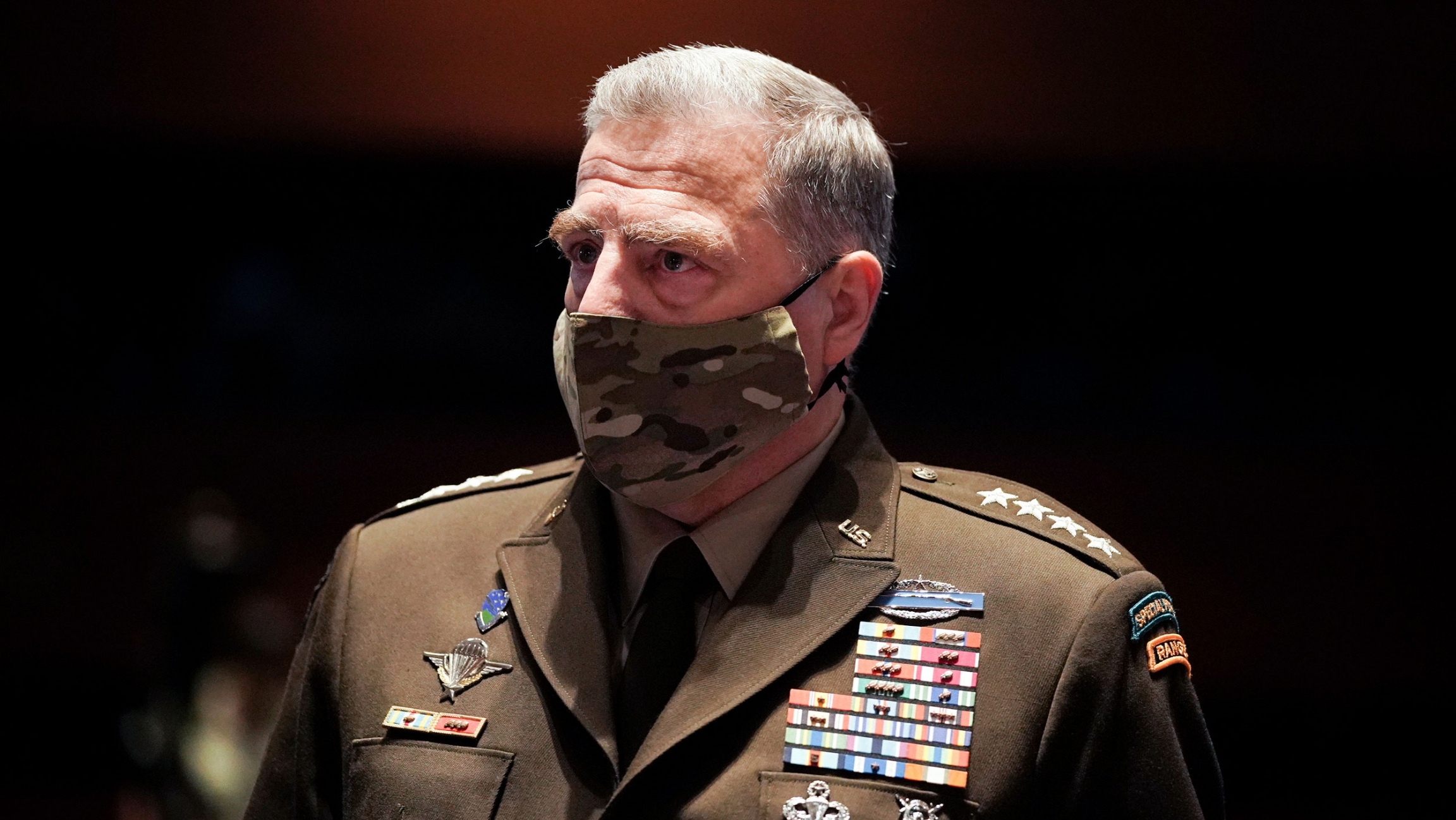 Chairman of the Joint Chiefs of Staff Gen. Mark Milley is shown wearing a camoflaged face mask and his military suit with medals across his chest.