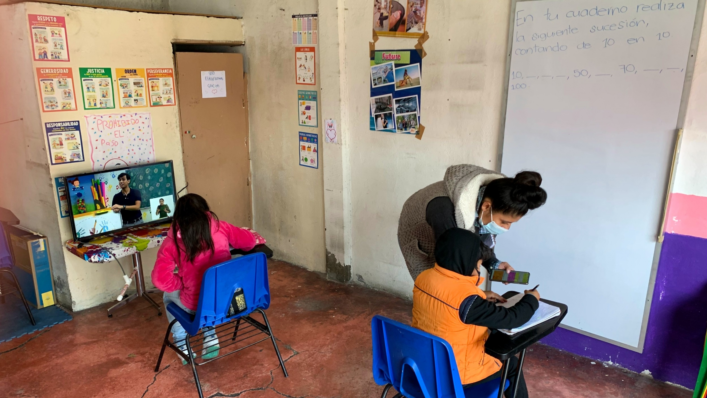 Dalia Davila, co-owner of La Abuela tortilla shop, helps Axel Carreño and Maria de la Luz Carreño at a space for students to use the internet and television for schooling.
