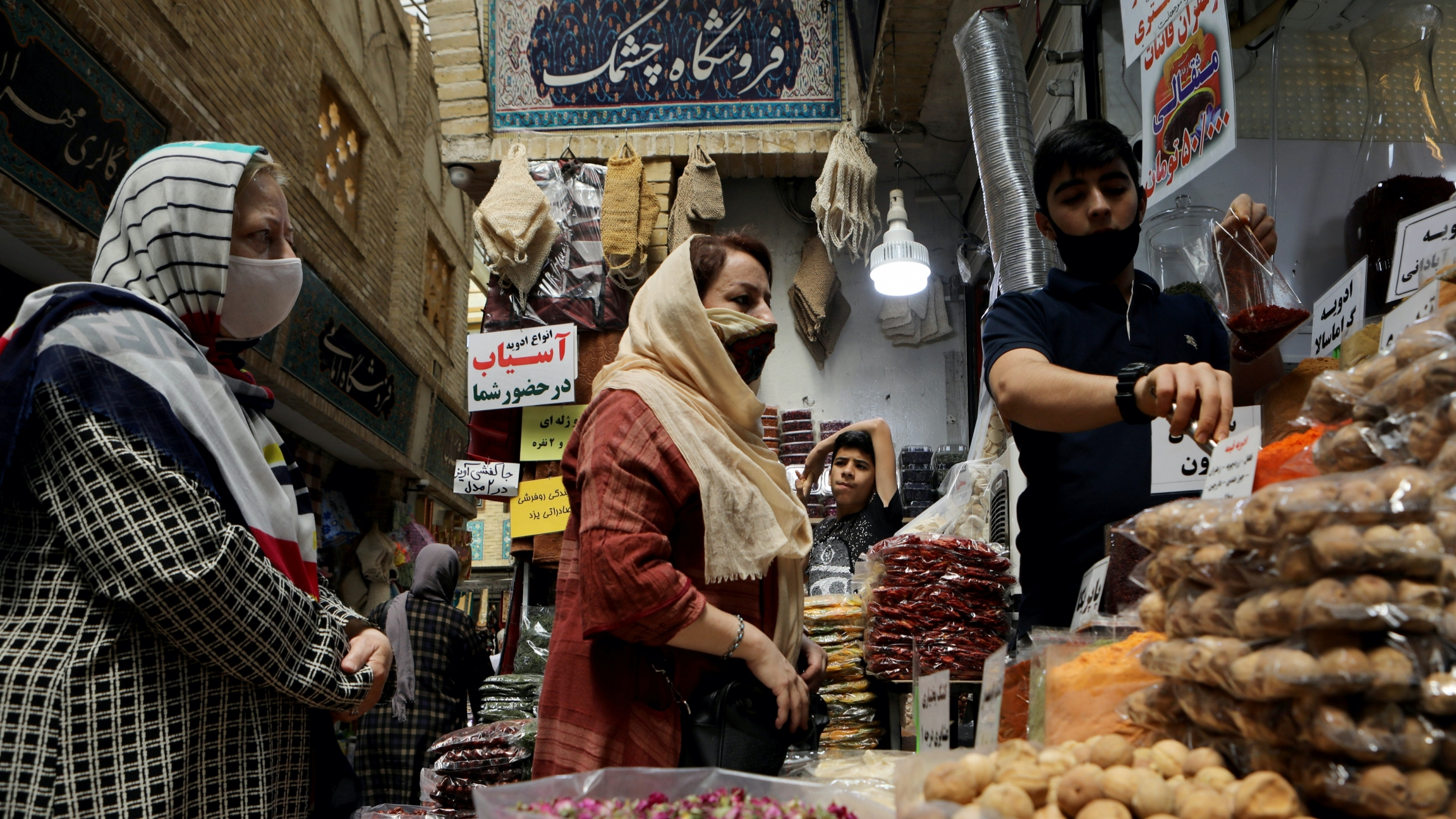 Three women wearing masks shop at a busy market with overflowing plastic packages of nuts