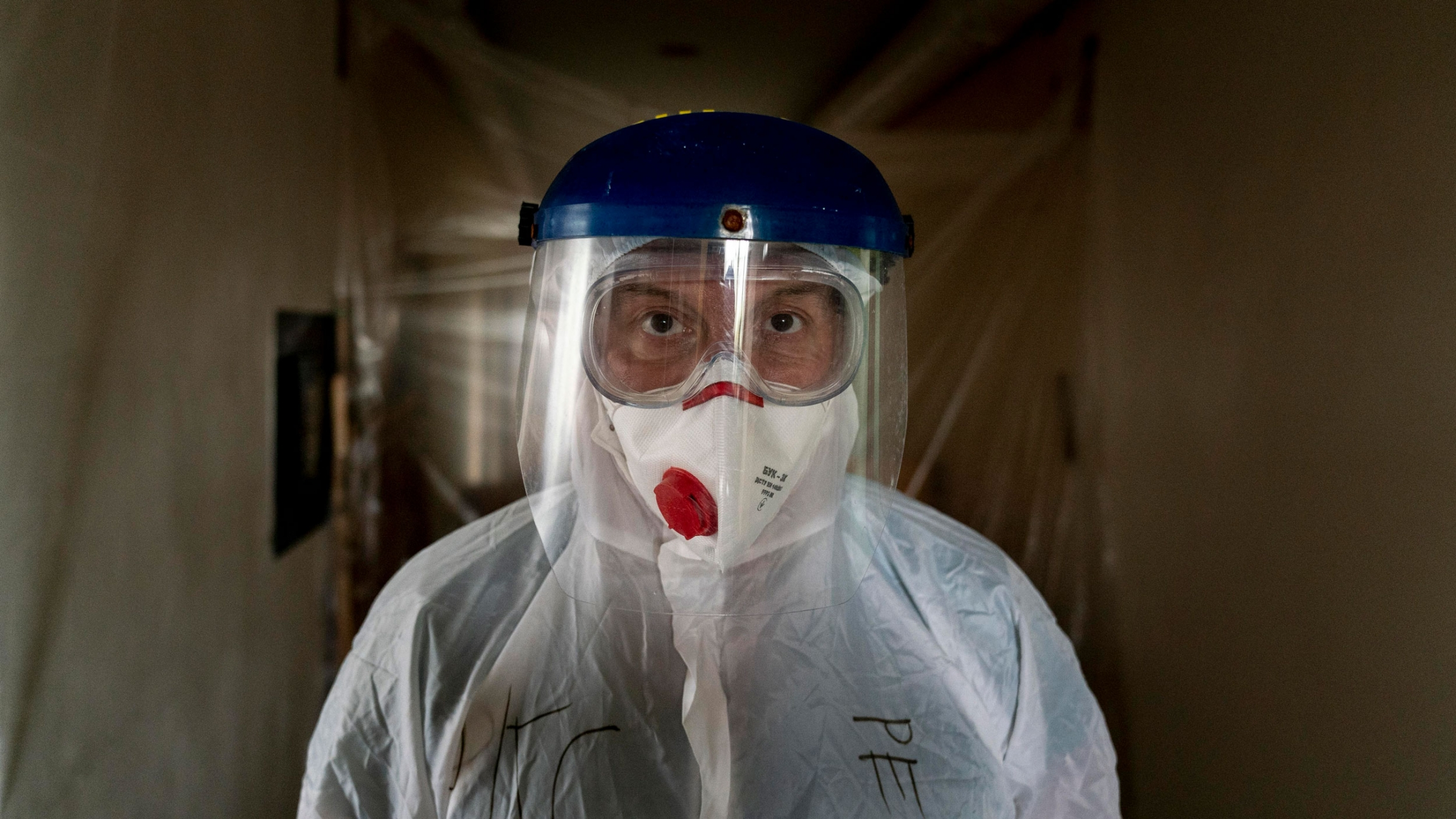 A doctor is shown looking directly into the camera and wearing goggles, a face mask and a face shield.