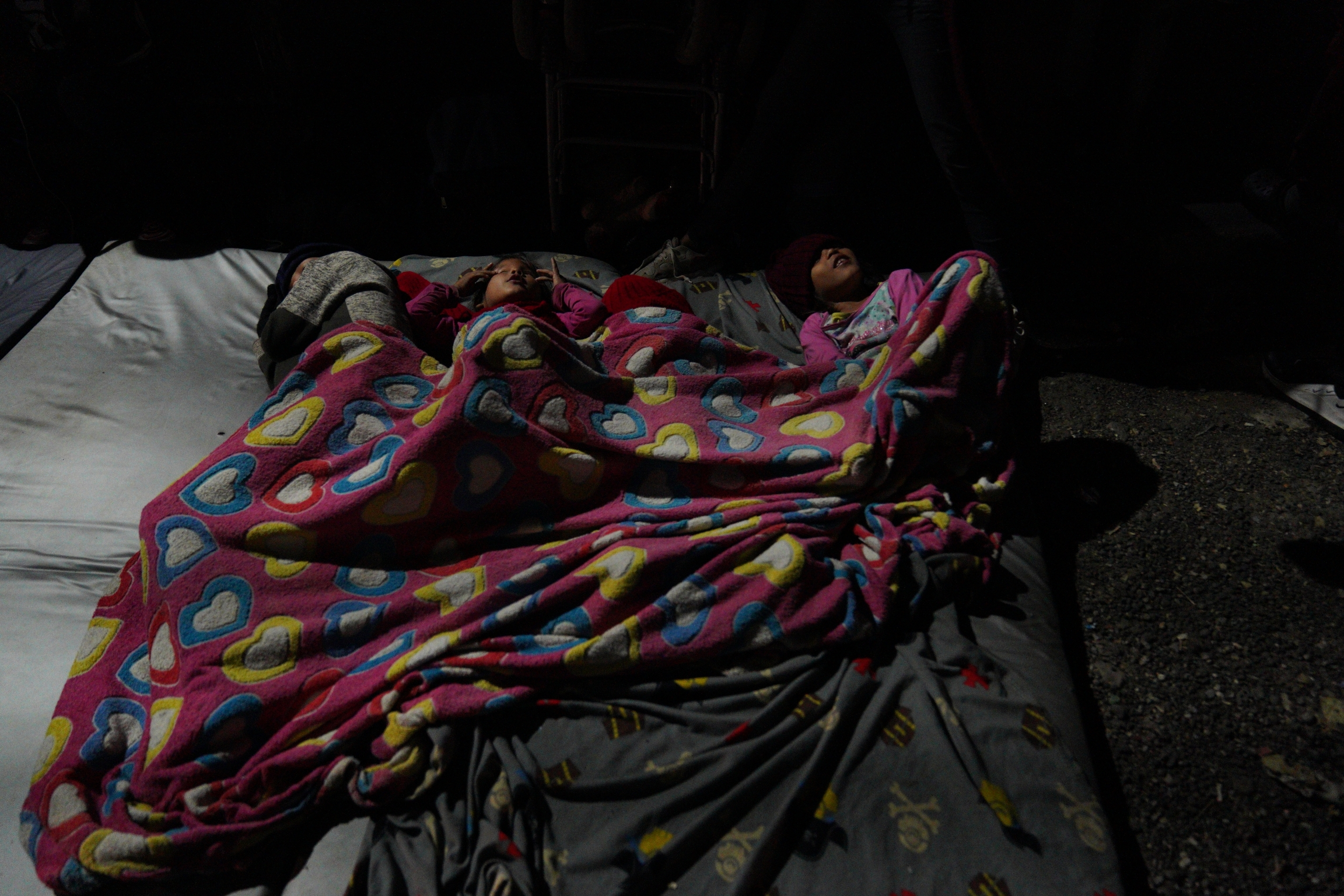 A family sleeps in a blanket on the street.