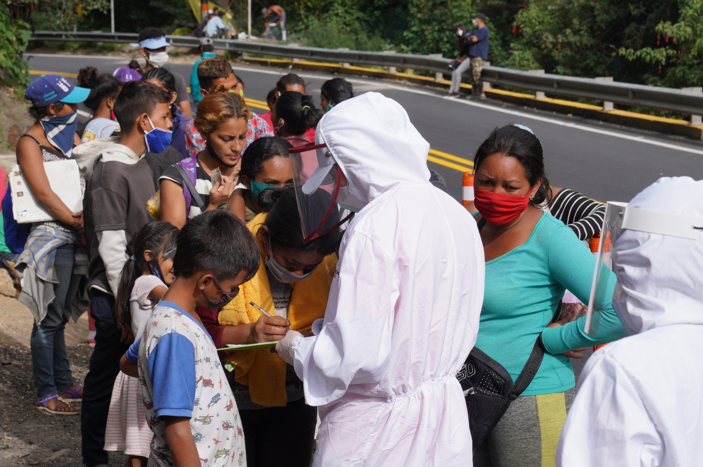 A humanitarian worker registers Venezuelan migrants arriving in Pamplona, Colombia, on Sept. 30. Social workers say that 200 migrants are passing through the country each day.