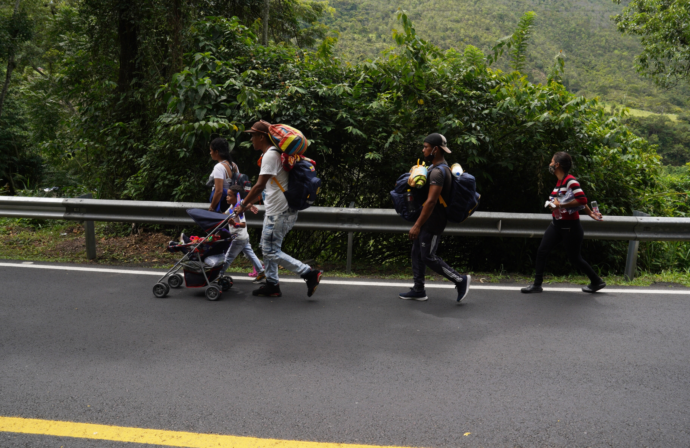 A family from Caracas, Venezuela walks along the road leading to Pamplona, Colombia, on Sept. 30. This family was heading to Ecuador where they had been promised work on a farm.