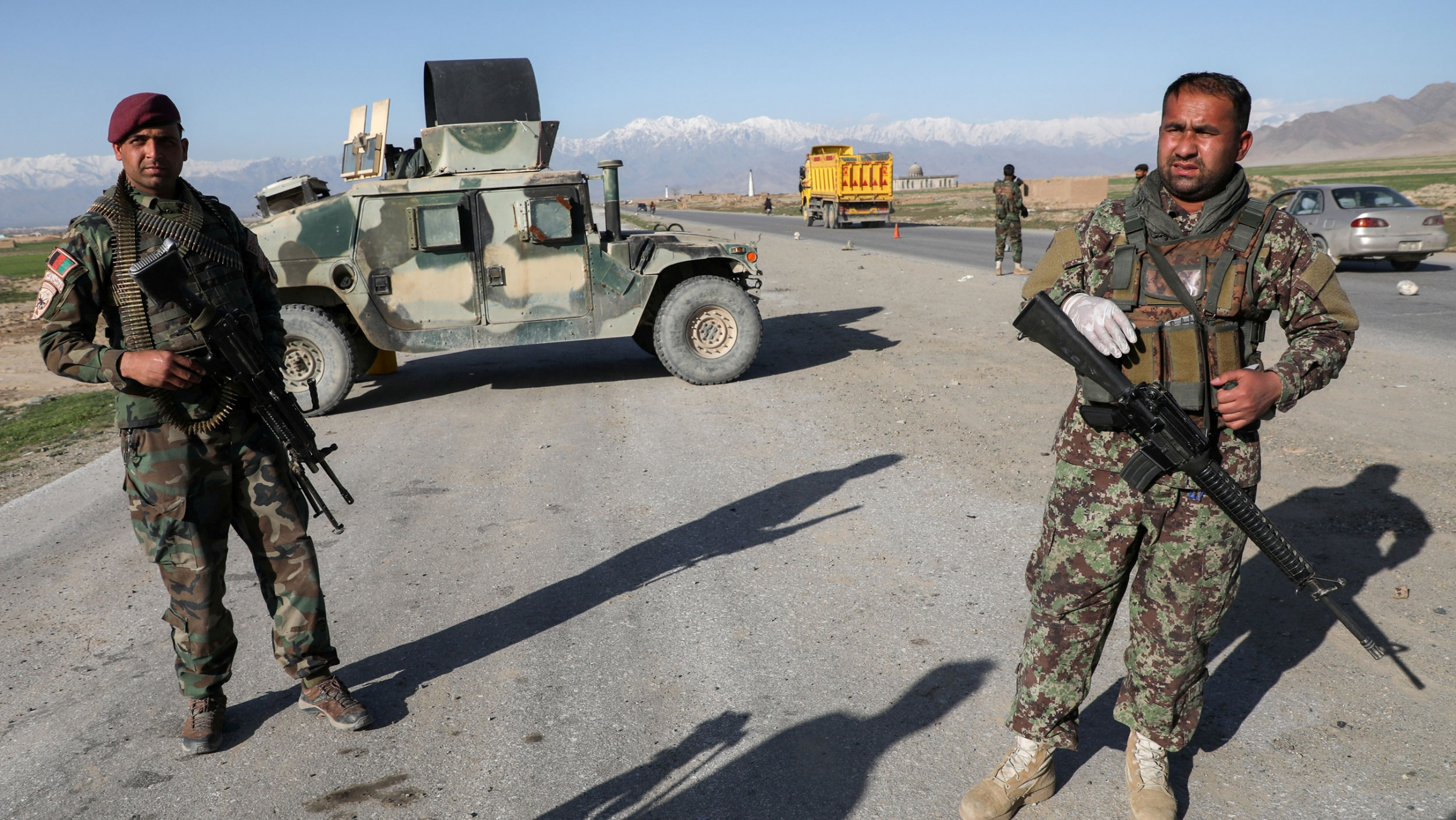 Two soldiers are shown standing near a road and holding weapons with an armored vehicle parked behind them.