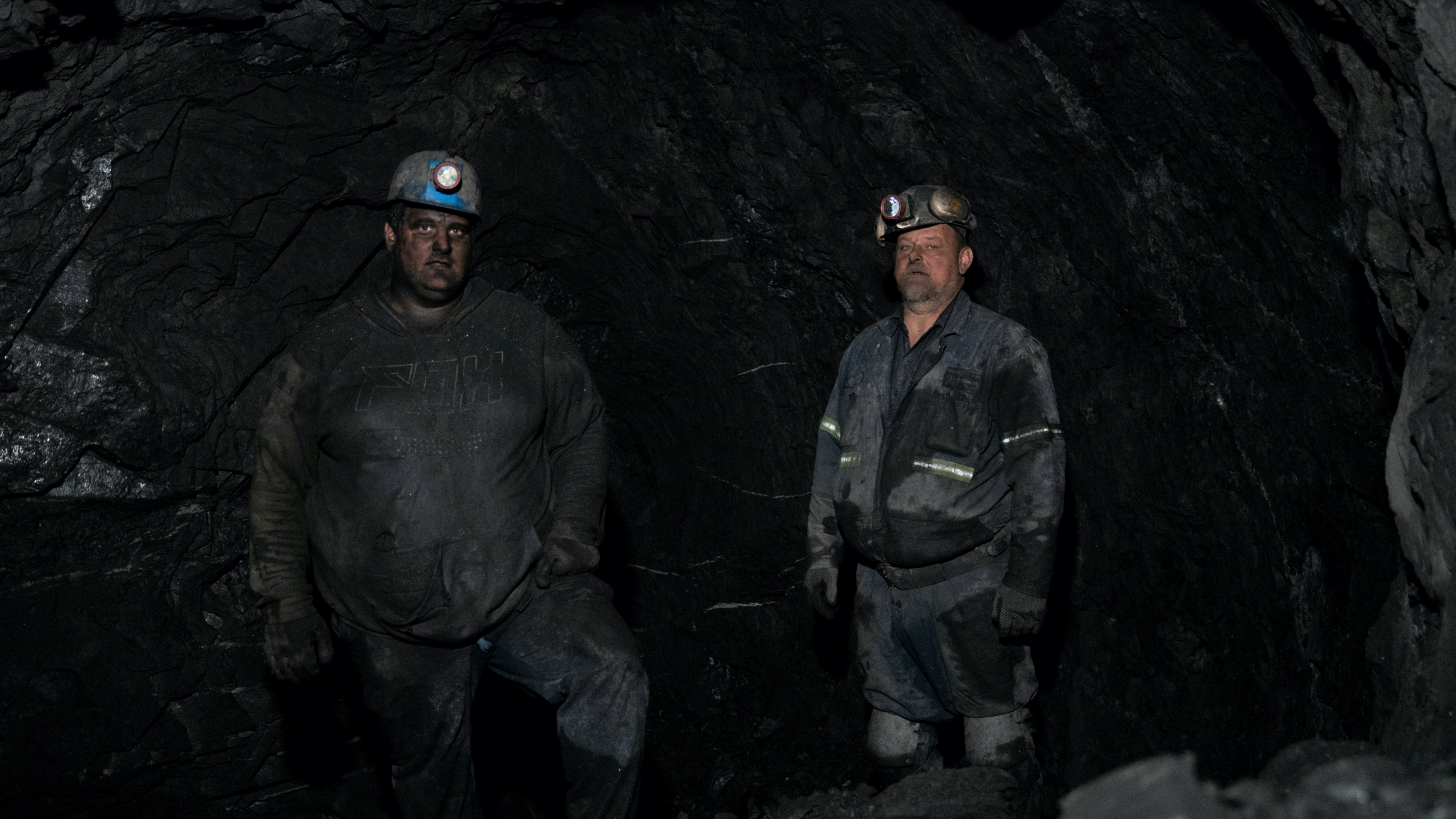 Two coal miners in uniform with skinned blackened from coal mining.