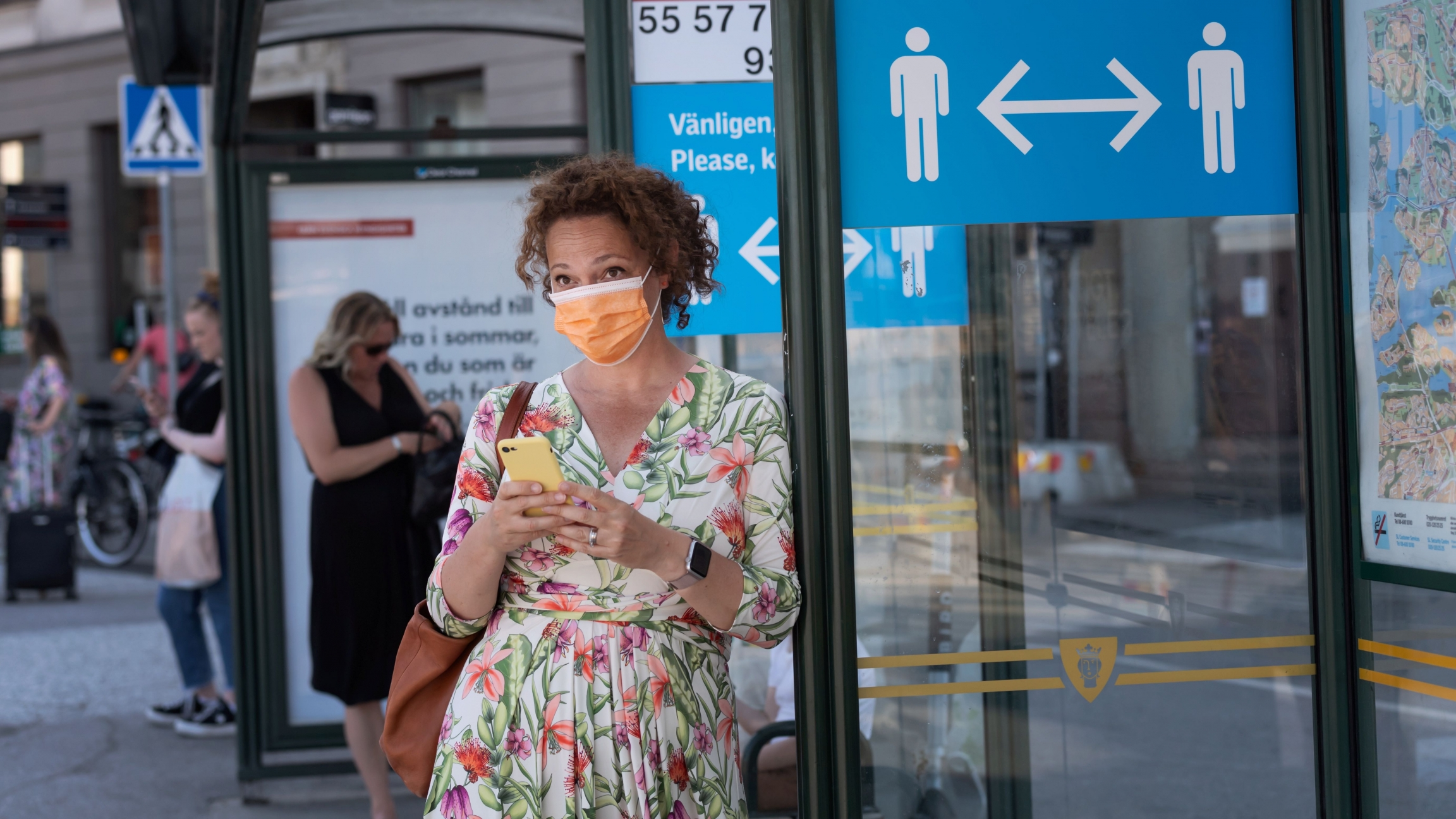 A woman wearing a face mask is seen in a bus stop next to an information sign asking people to keep social distance due to the outbreak of the coronavirus disease (COVID-19), in Stockholm, Sweden, June 26, 2020.