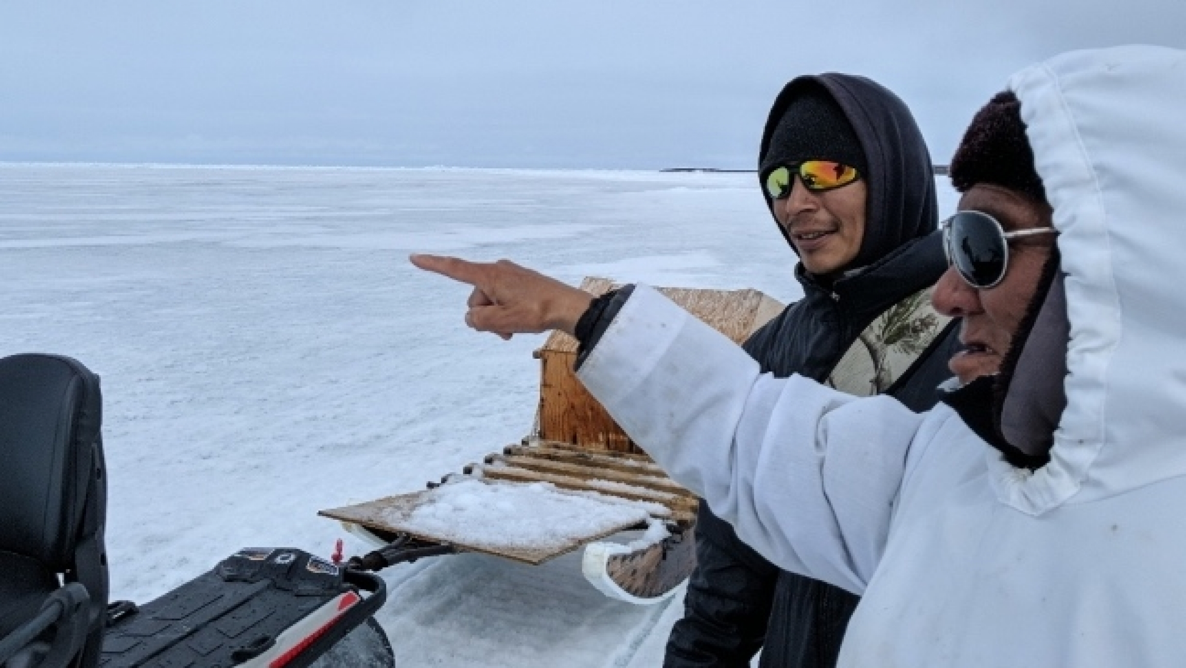 An elder wearing sunglasses and a white coat points off into the Arctic distance while standing by another man wearing sunglasses.