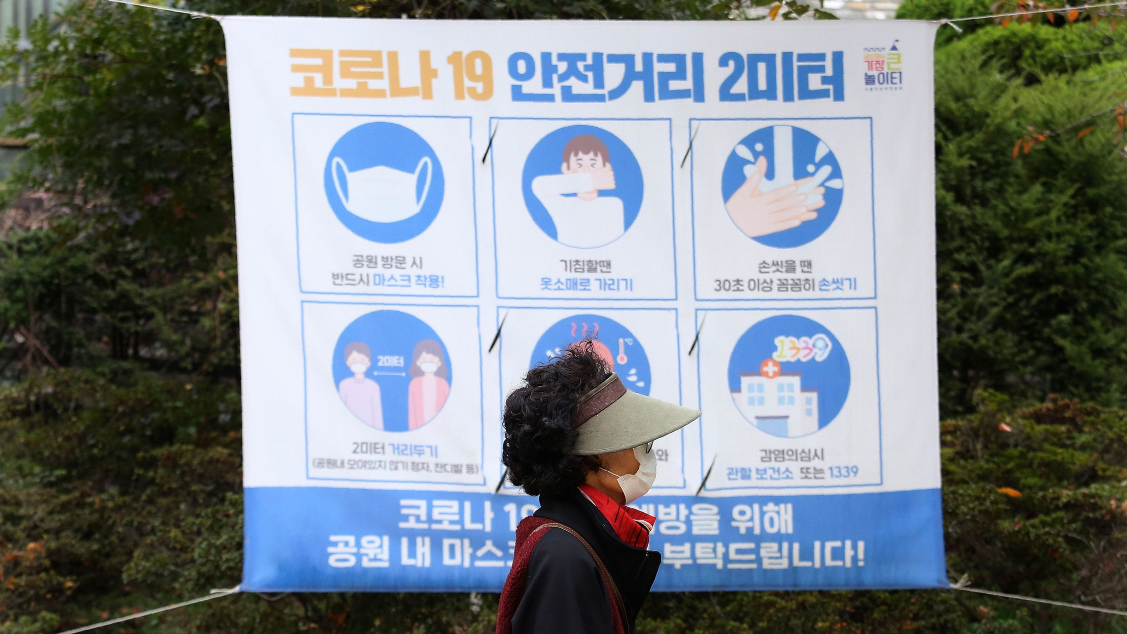 A woman is shown wearing a visor and face mask while walking past a poster with guidance on stopping the spread of the coronavirus.