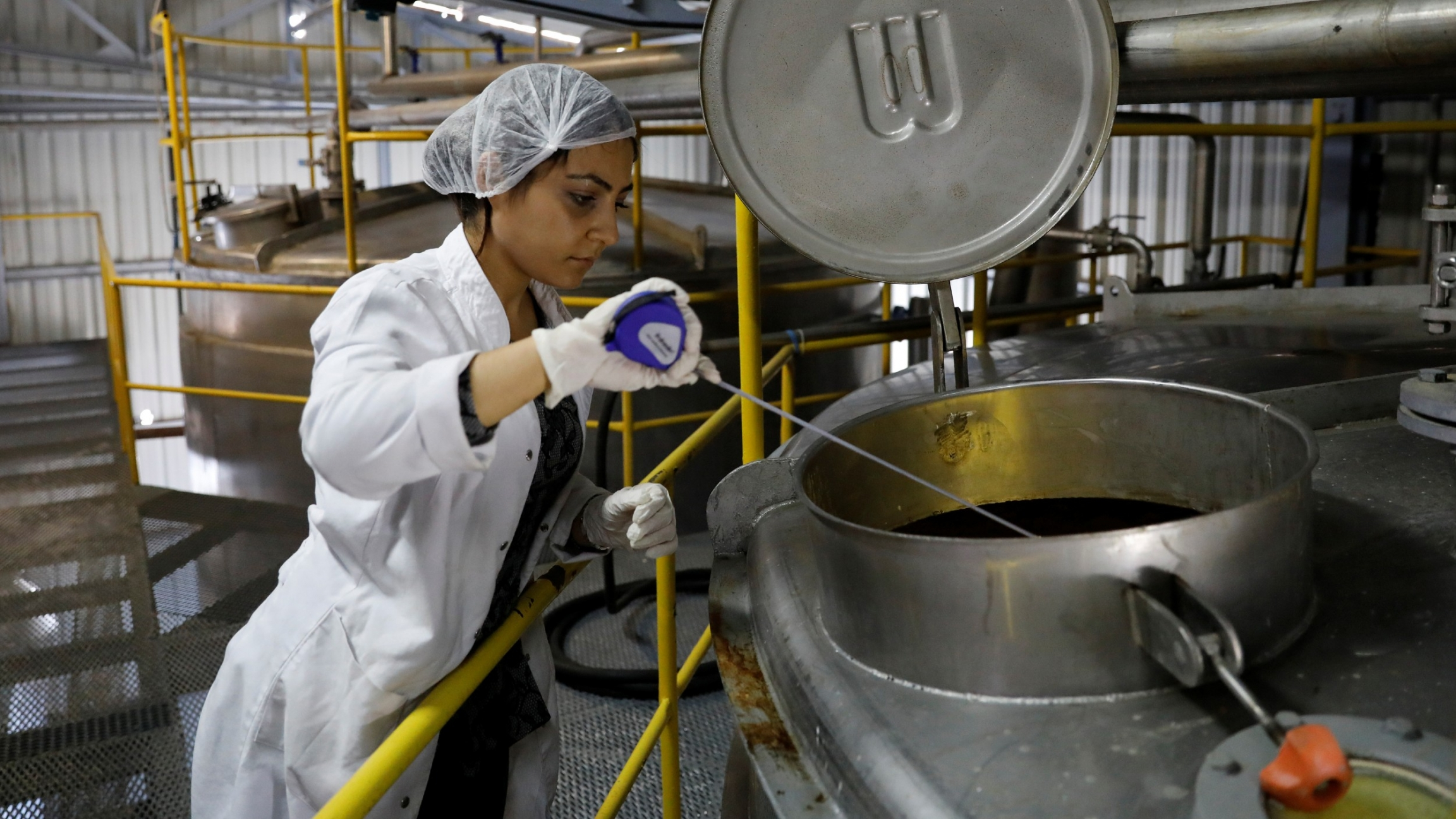 In this file photo, an employee takes a sample from a storage cylinder of Turkey's popular alcoholic drink rakı at the Infotex Alkollu Icecekler plant in the town of Dinar, Turkey, Nov. 30, 2017.