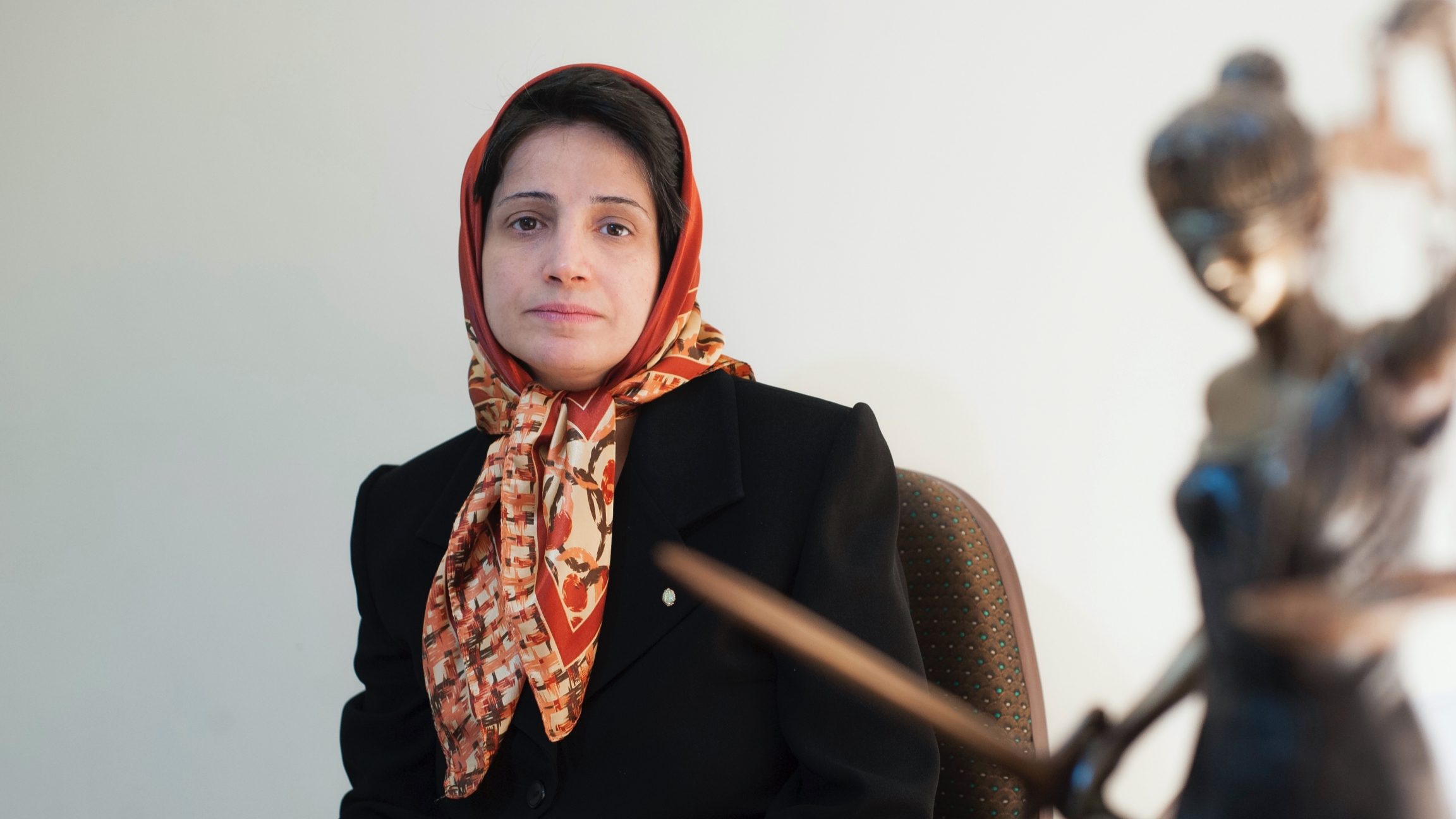 A woman wearing a head scarf sits at her desk and poses for a photograph.