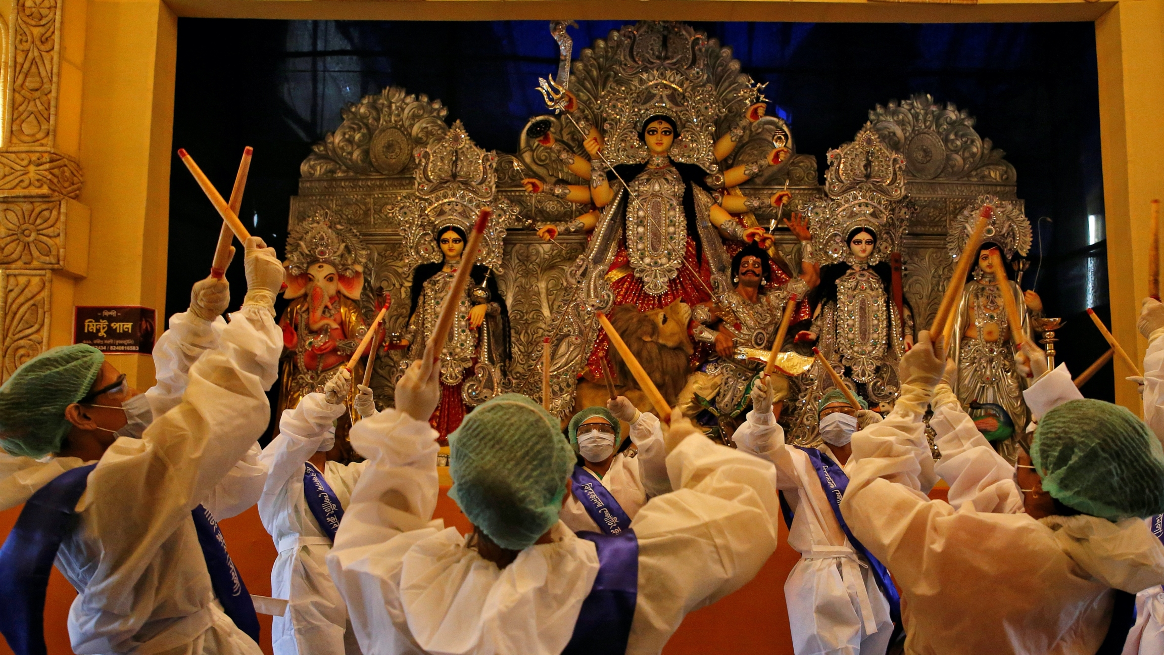 People wearing protective gear worship in front of a 10-armed ornate goddess idol on a platform.