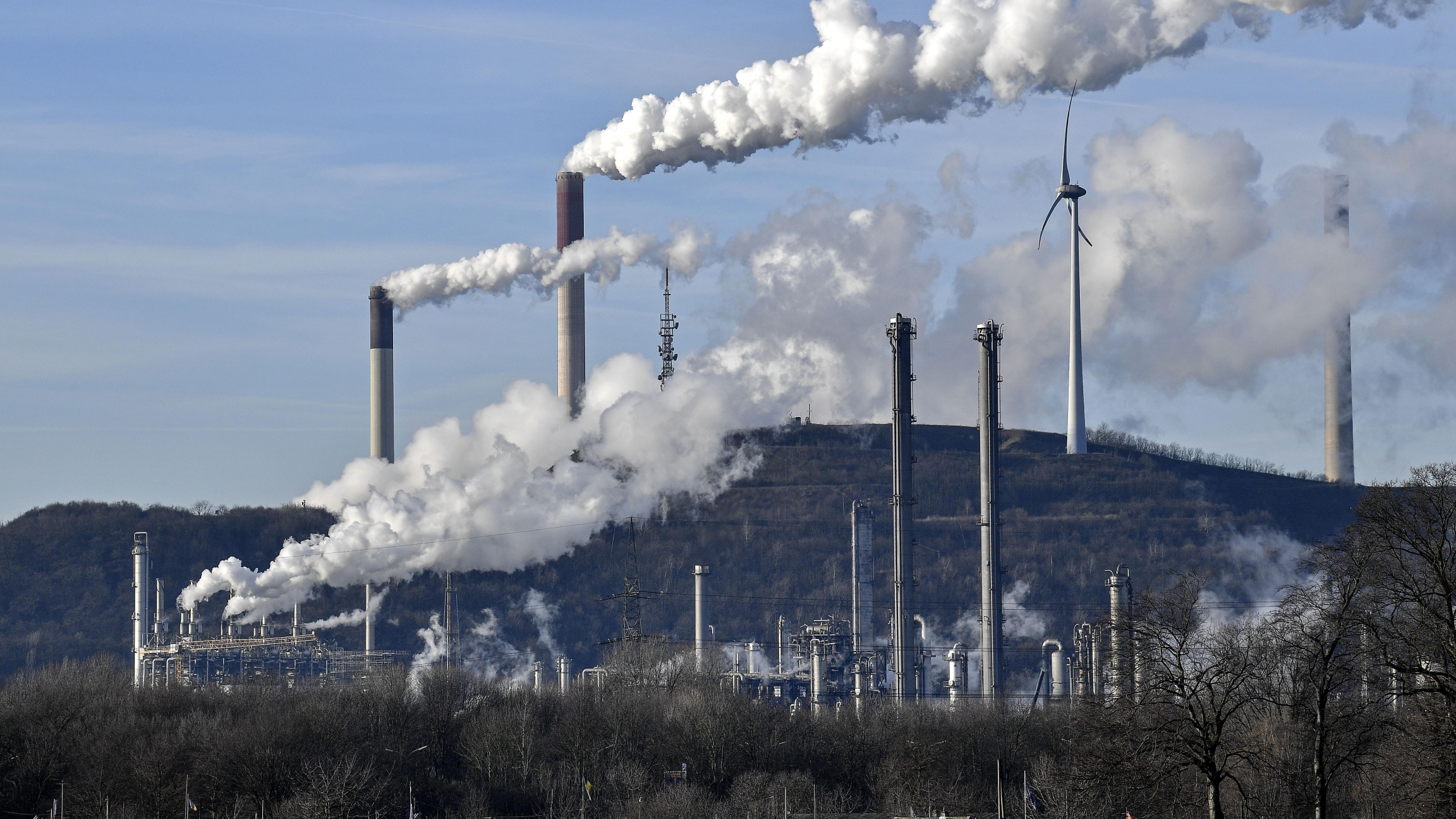 In this Jan. 16, 2020, file photo an uniper coal-fired power plant and BP refinery steam beside a wind generator in Gelsenkirchen, Germany.