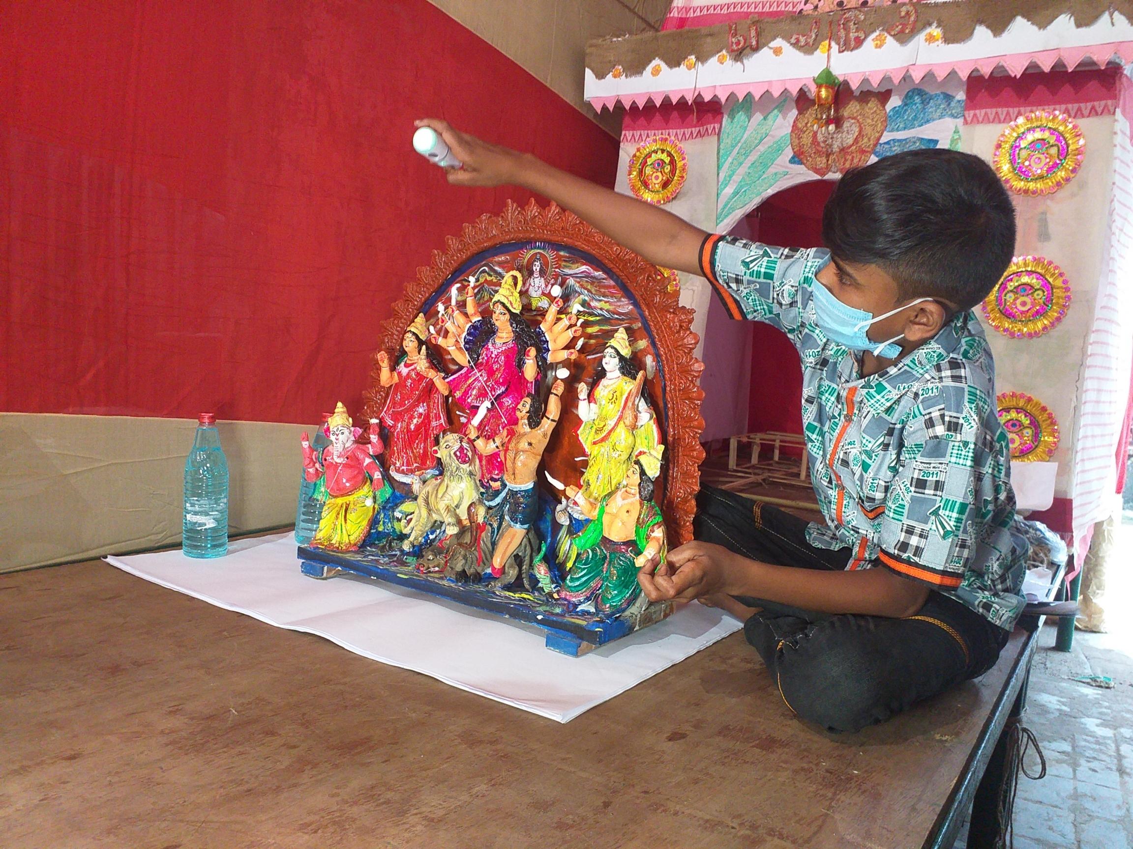 A little boy sanitizes a small idol.