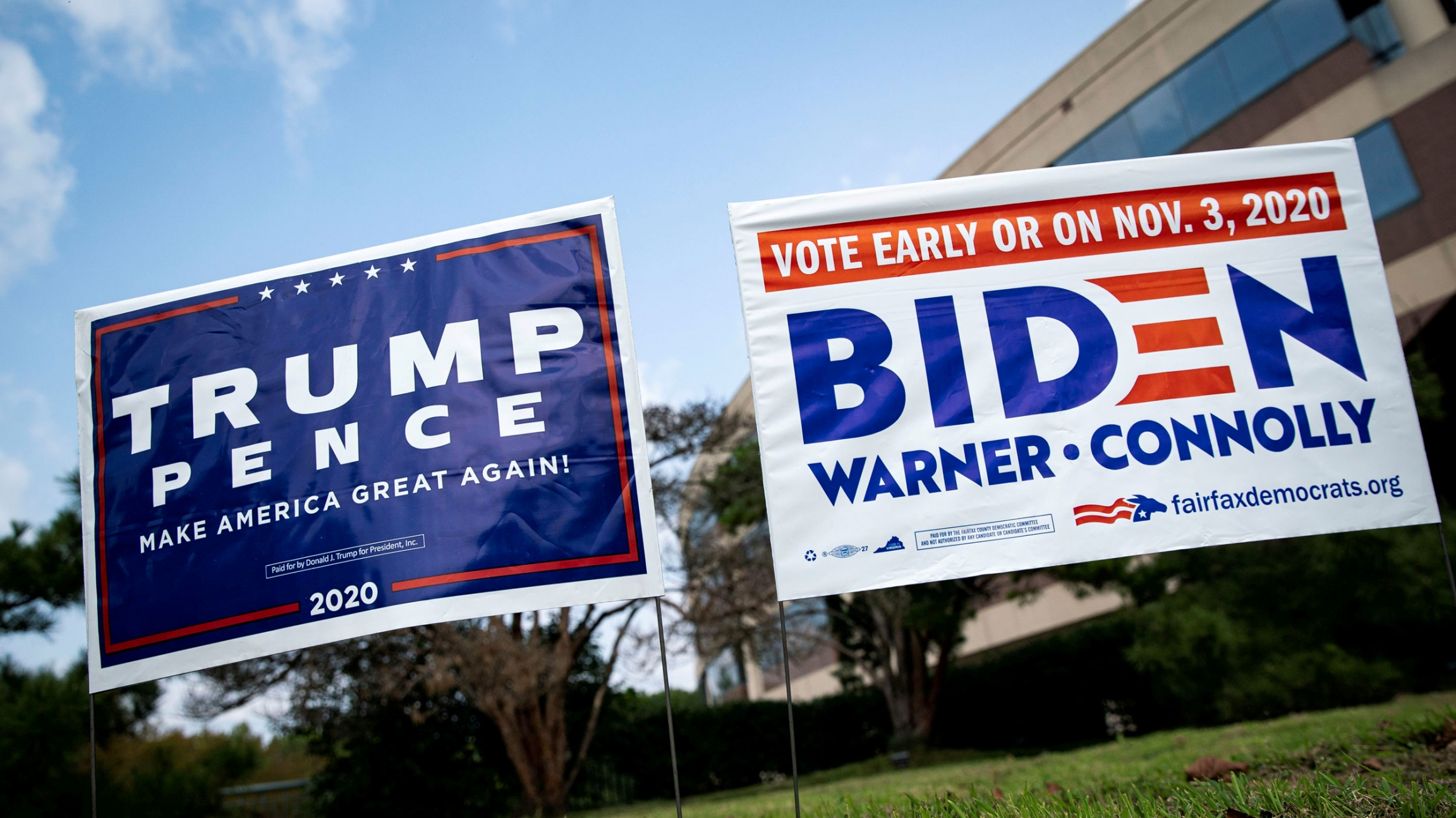 Two political yards signs are shown side-by-side — a mostly blue-colored Trump sign and a white with blue lettering Biden sign.