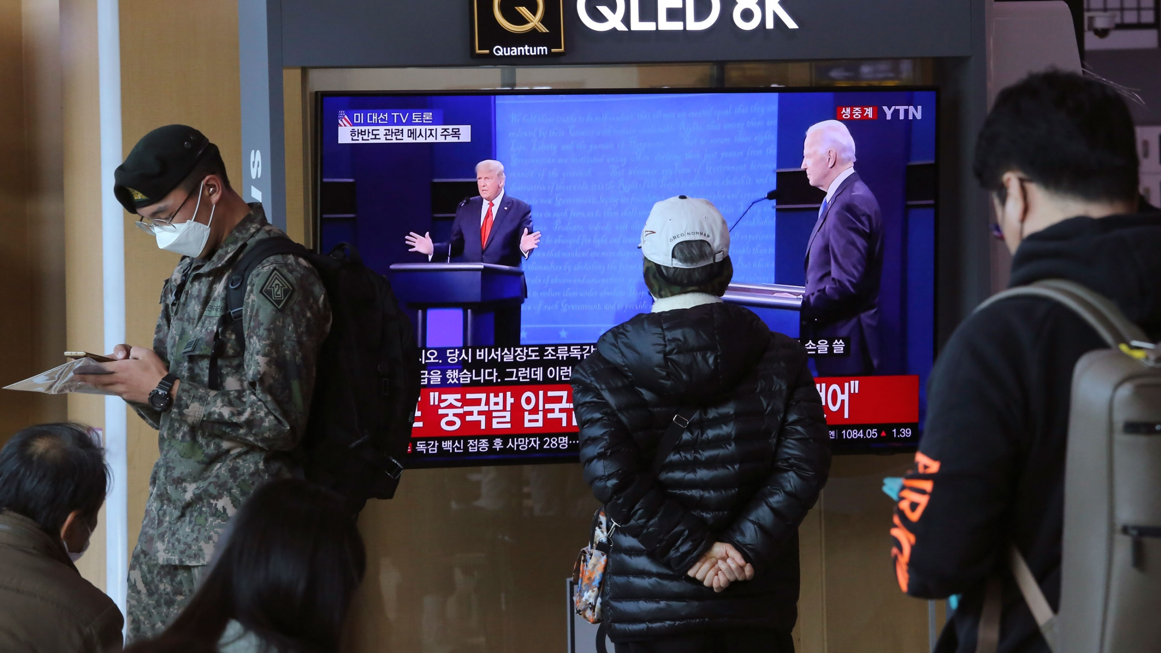 Several people are shown standing near and one person watching a TV screen showing the US presidential debate.