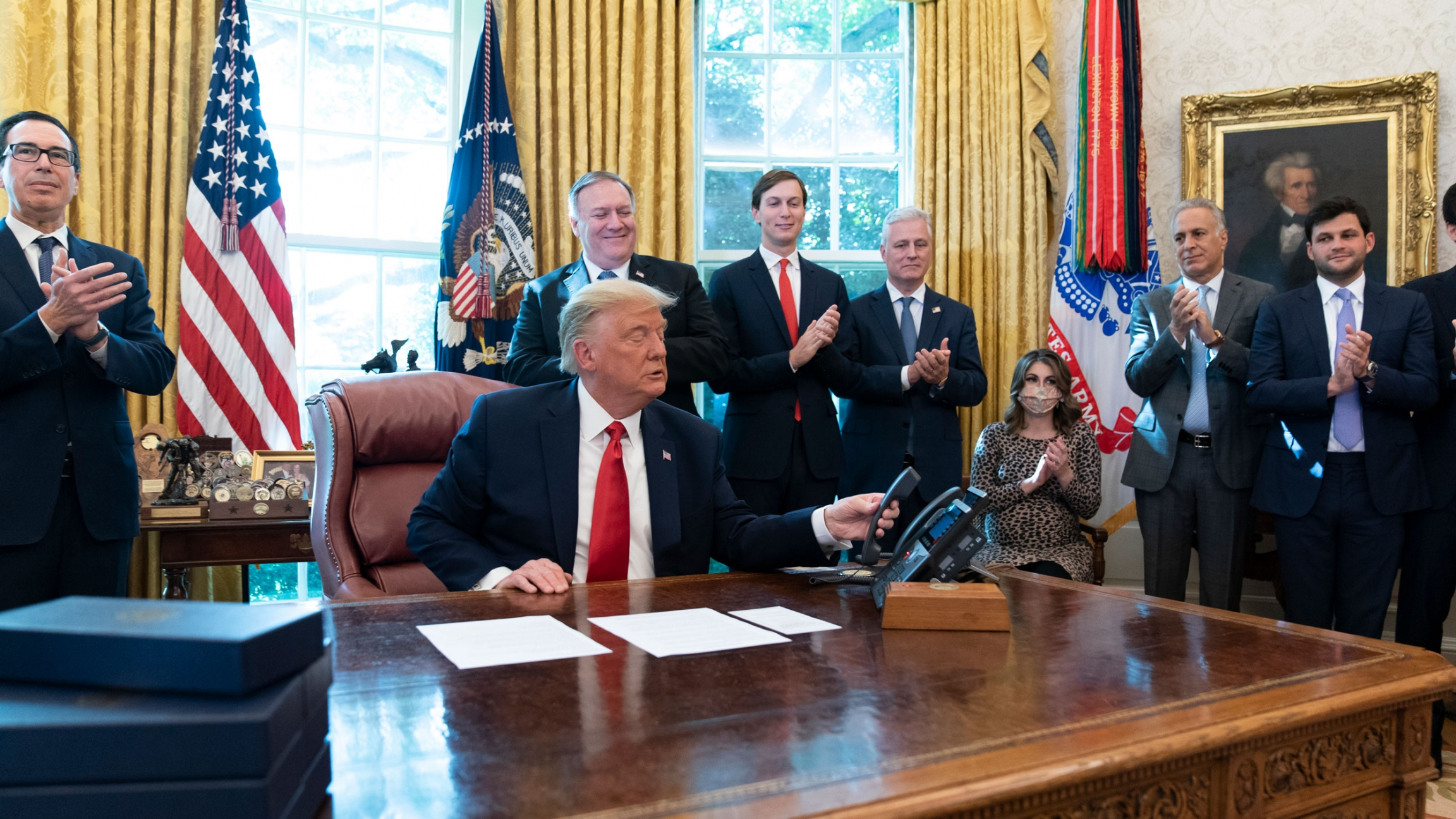 Donald Trump is shown sitting at a desk and wearing a dark suit with a red tie and hanging up a phone.
