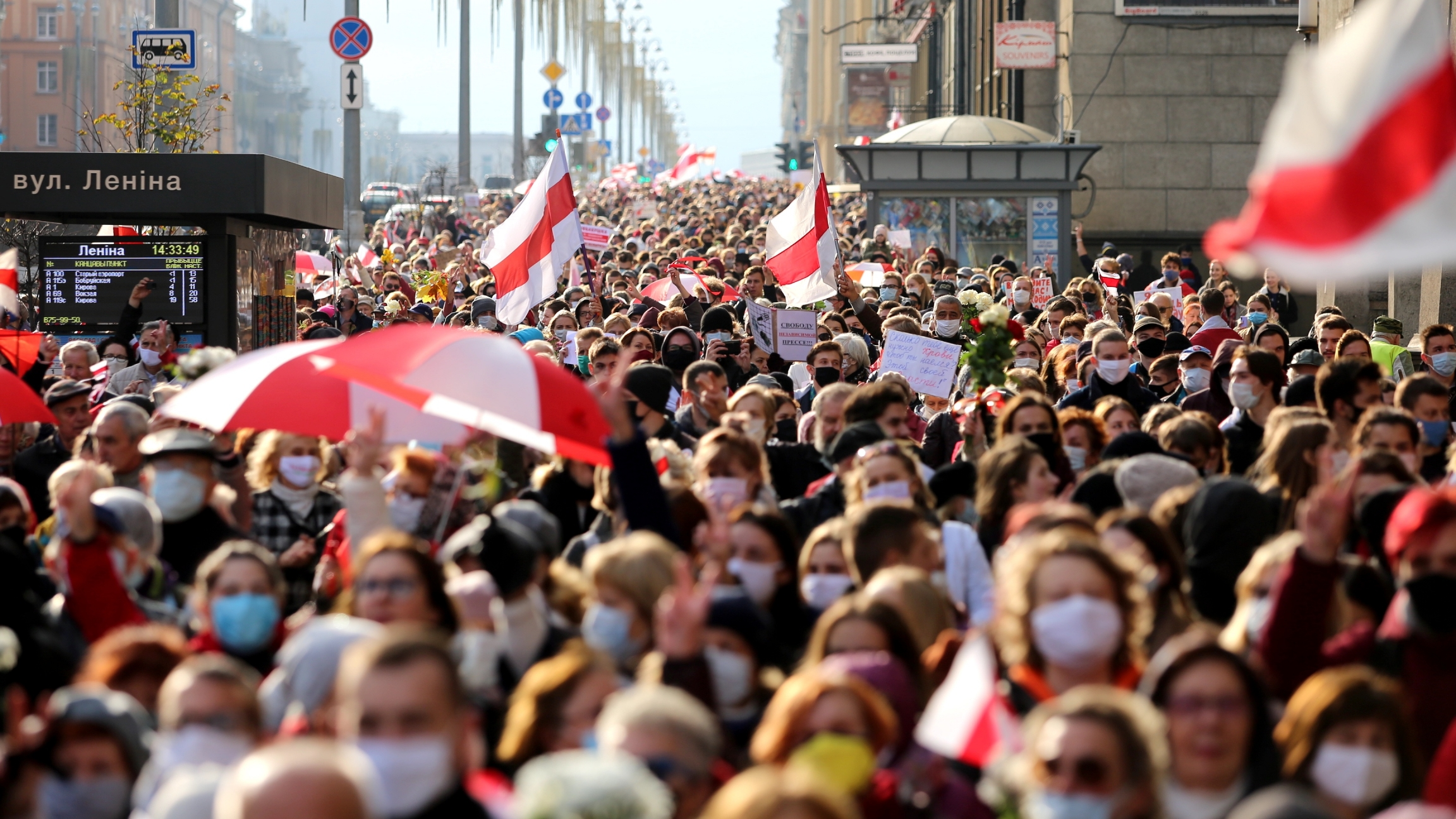 Mass of people wearing masks march with red and white umbrellas.