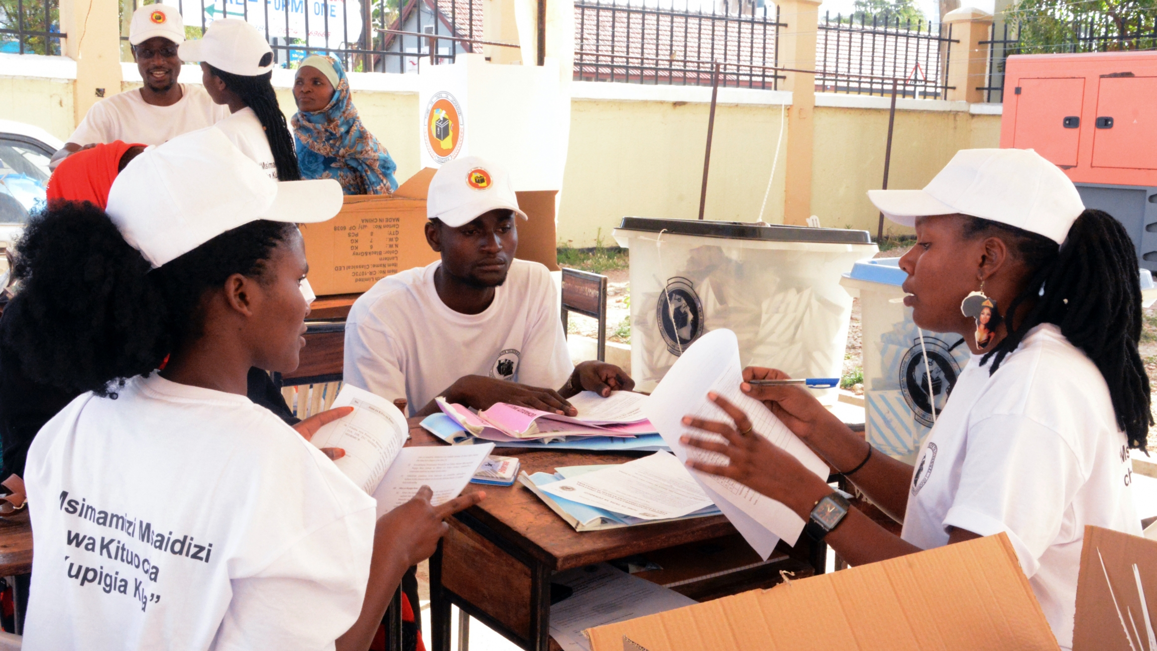 Three poll workers wearing white shirts and hats sit at a table together and sort through papers