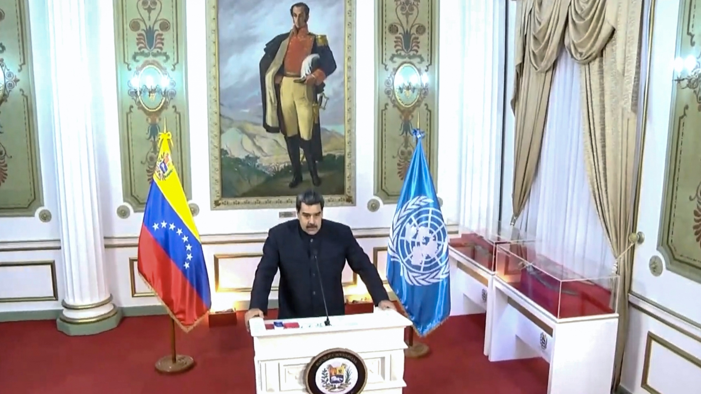 Maduro speaks at a white podium flanked by two flags in a decorative room with a painting of a uniformed man behind him.