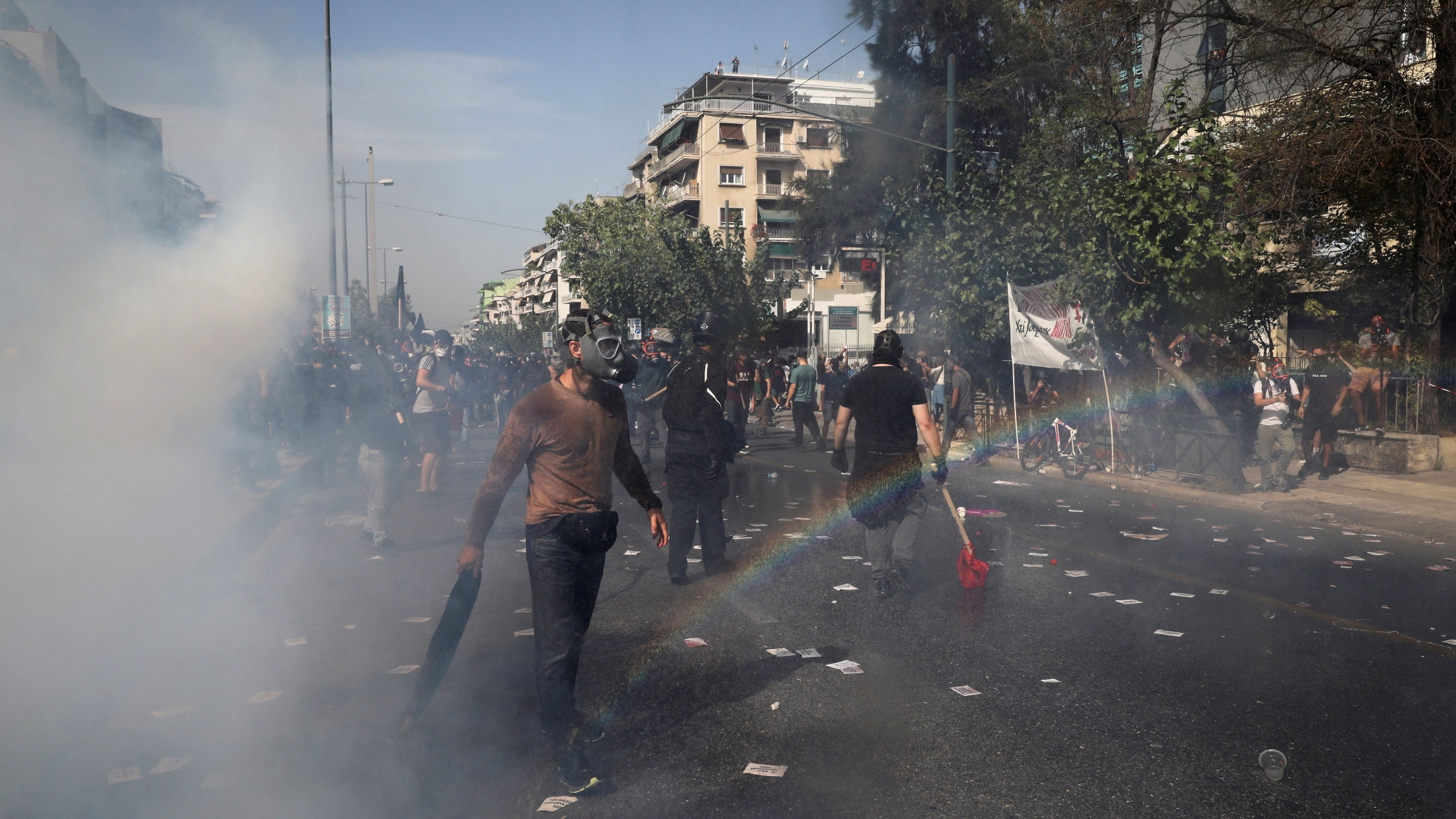 Protesters are seen among tear gas during clashes outside a court, where the trial of leaders and members of the Golden Dawn far-right party takes place in Athens, Greece, Oct.7, 2020.