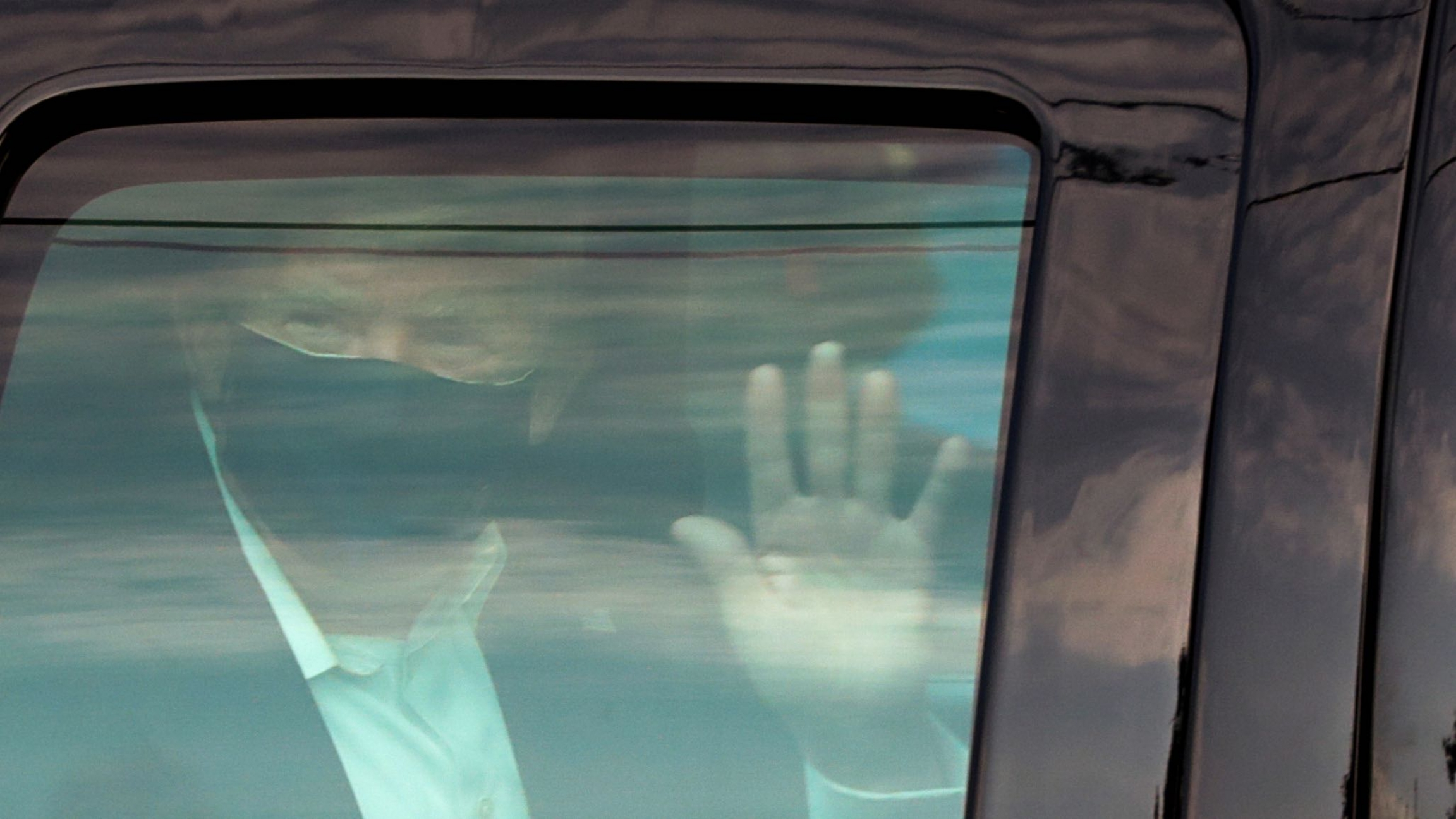 President Donald Trump waves to supporters as he briefly rides by in the presidential motorcade in front of Walter Reed National Military Medical Center, where he is being treated for the coronavirus in Bethesda, Maryland, Oct. 4, 2020.