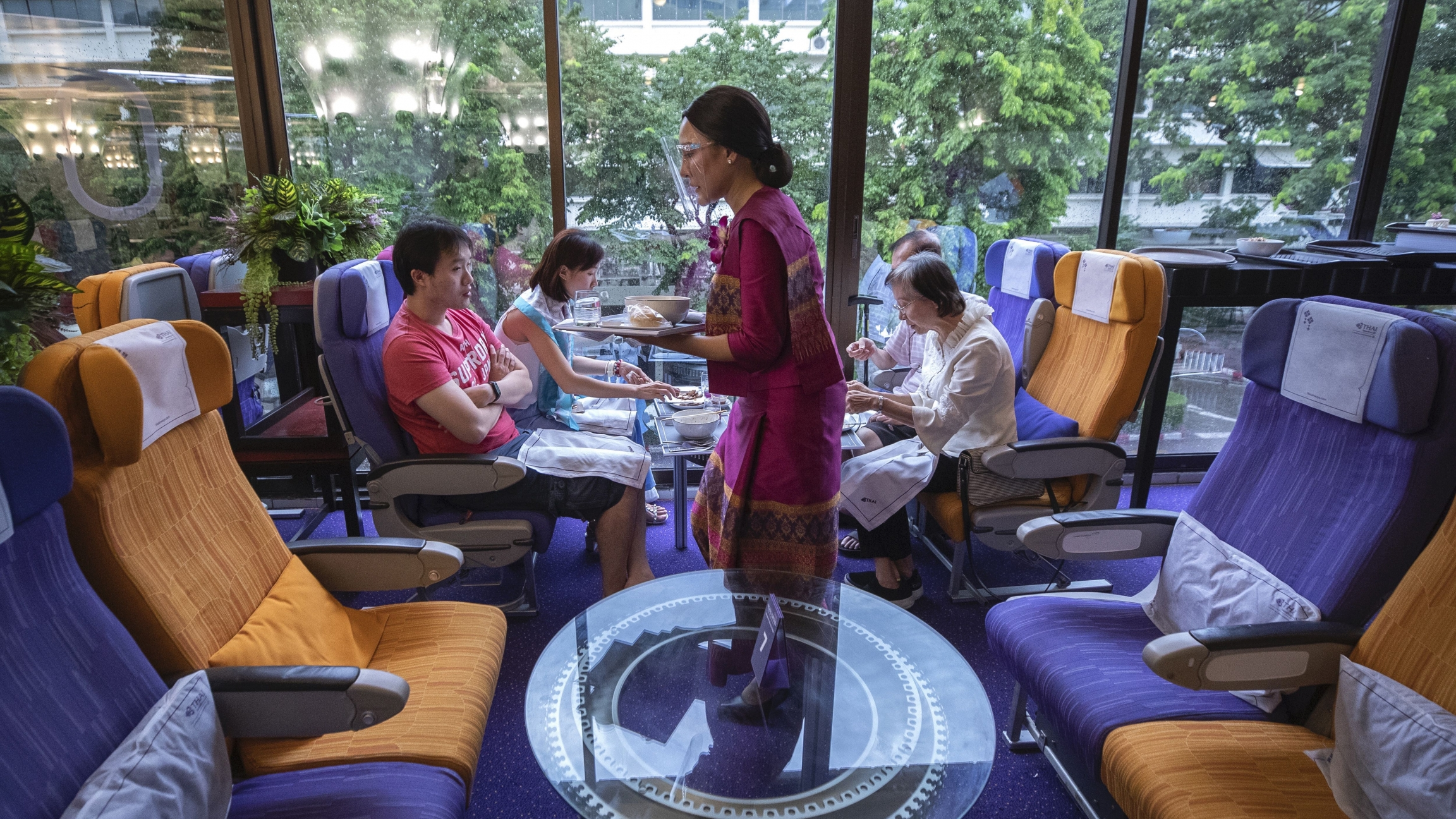 A flight attendant is serving meals in a flight-themed restaurant complete with airline seats and cabin crew to customers at Thai airways head office in Bangkok, Oct. 3, 2020.