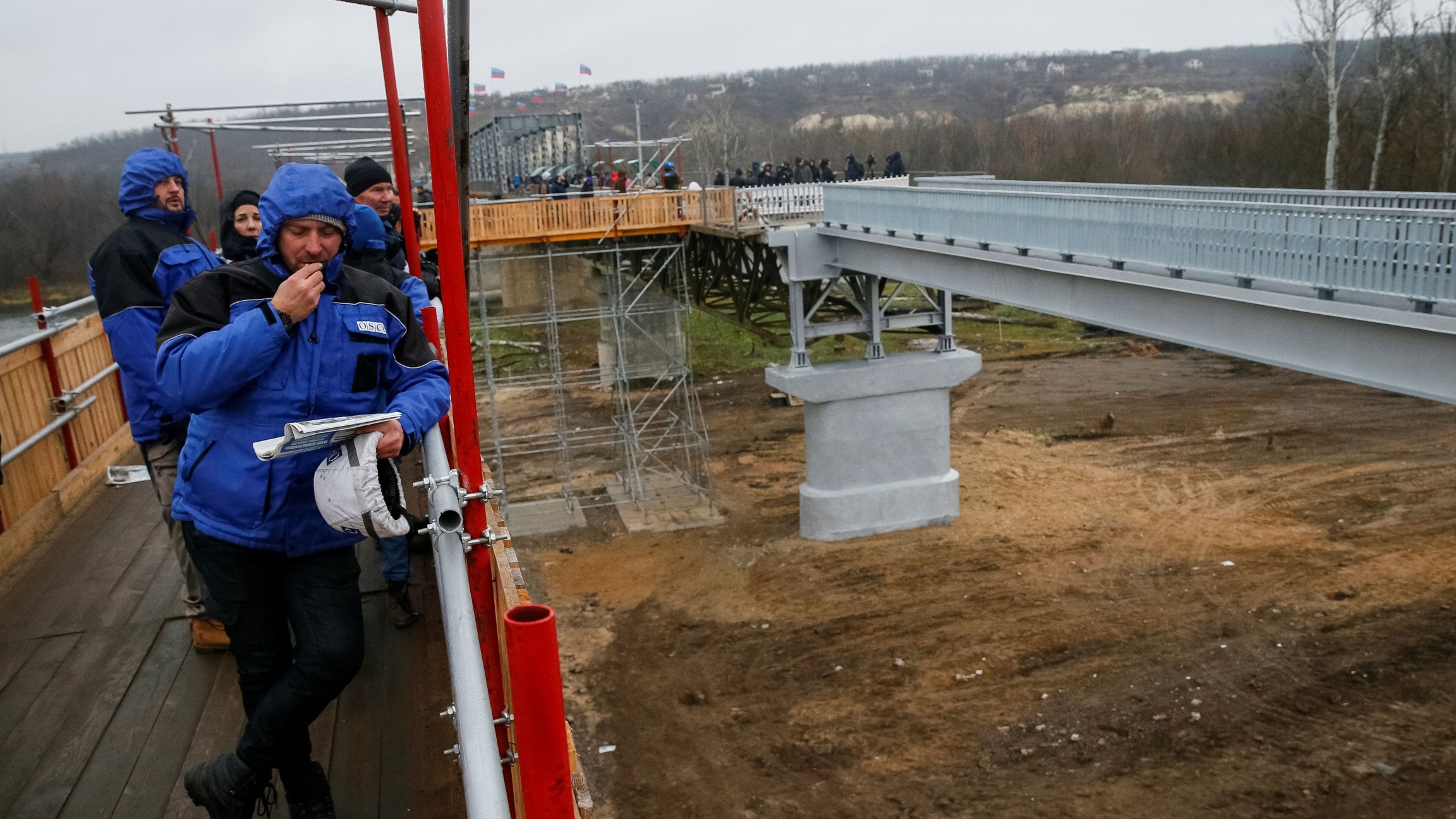 Members ofOrganizationforSecurityandCooperationinEurope(OSCE) look on as they visit a section of the restored bridge, which was blown up during a military conflict between Ukrainian government forces and Russian-backed rebels, in the settlement of