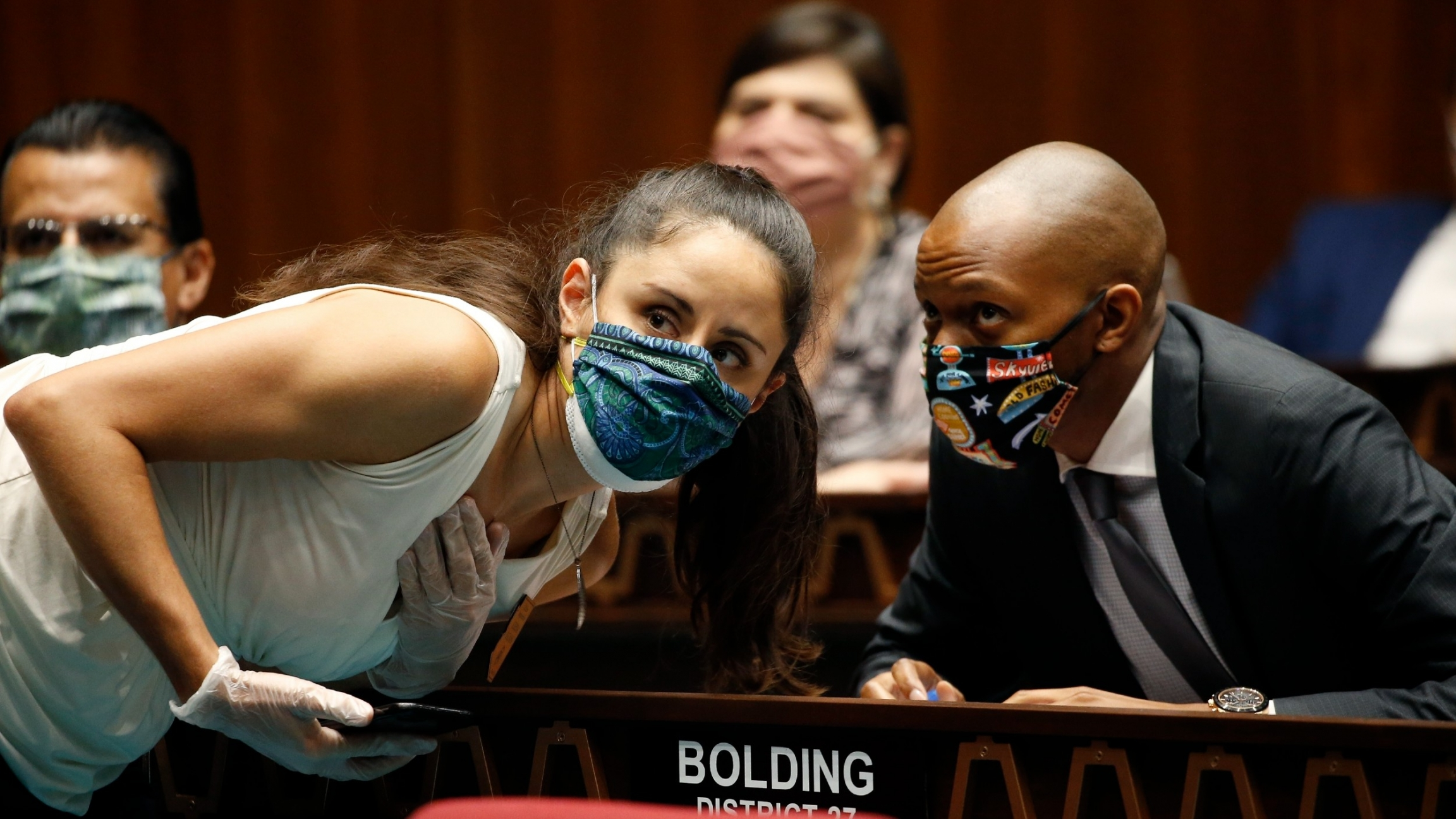 Rep. Athena Salman, left, talks with Rep. Reginald Bolding during a vote in the Arizona House of Representatives to end the 2020 session due to the coronavirus, May 19, 2020, in Phoenix.