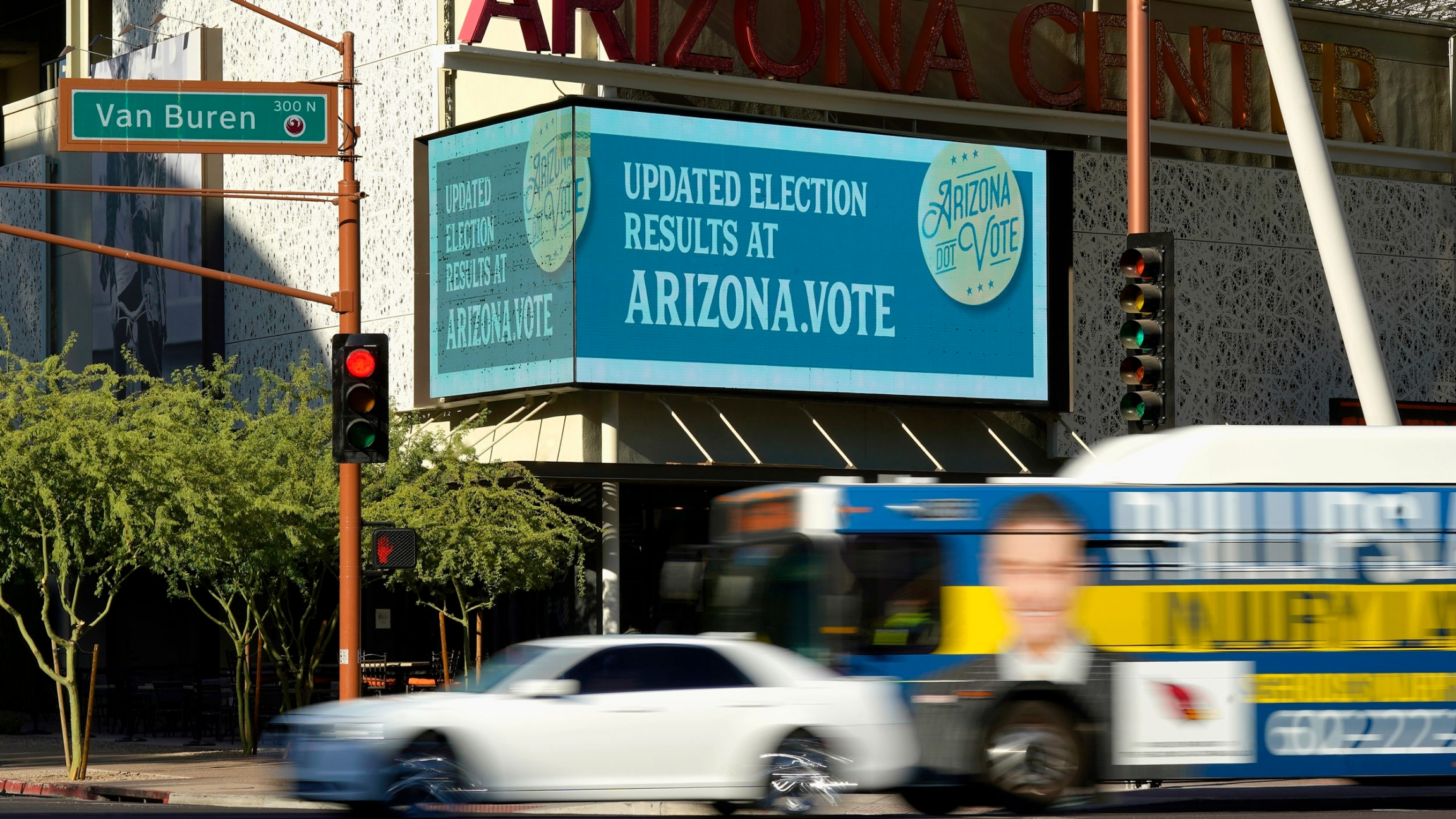 An electonic billboard is shown with information about the Arizona vote as vehicles pass by.