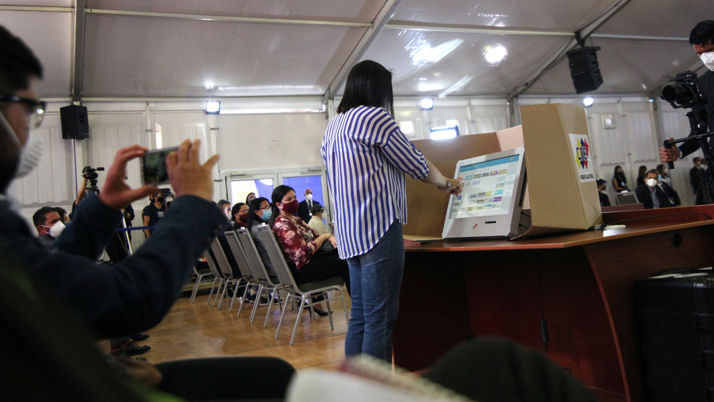 A woman simulates her vote as Venezuela's National Electoral Council presents the technology platform forparliamentary elections in Caracas,Venezuela, Oct.9, 2020.