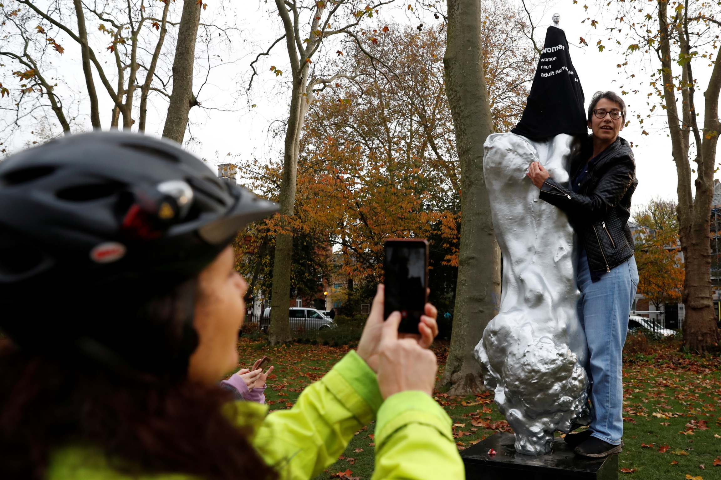 A protester covers with a T-shirt the Mary Wollstonecraft statue by artist Maggi Hambling, in Newington Green, London, Britain, Nov. 11, 2020.