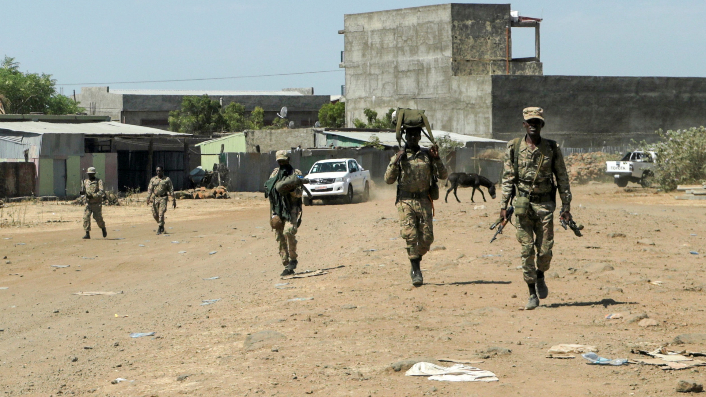 A small group of soldiers are shown walking and carrying weapons with a large cement structure in the distance.