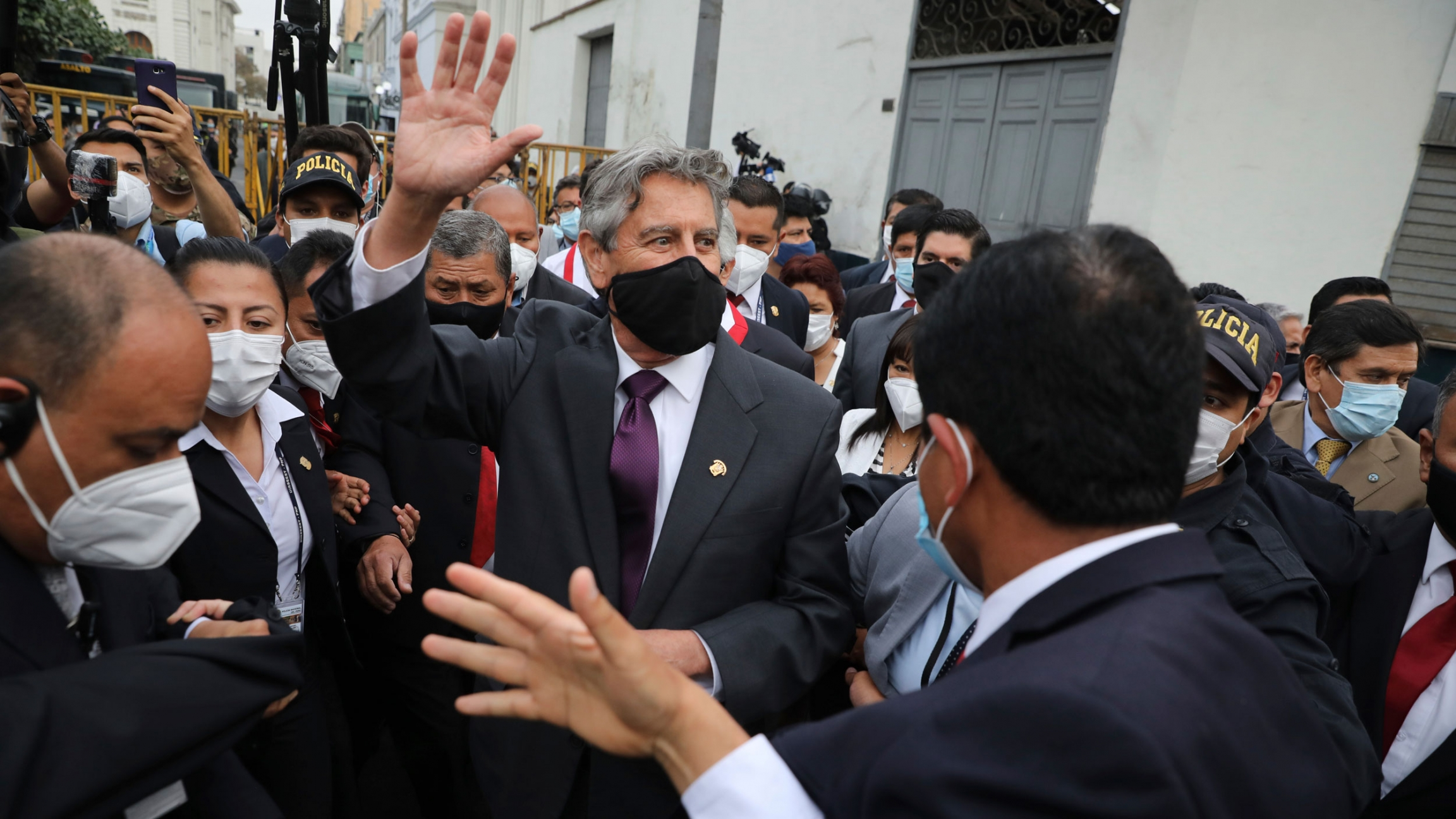 Peru's new President Francisco Sagasti is shown among a large crowd of people while wearing a face mask and waving.