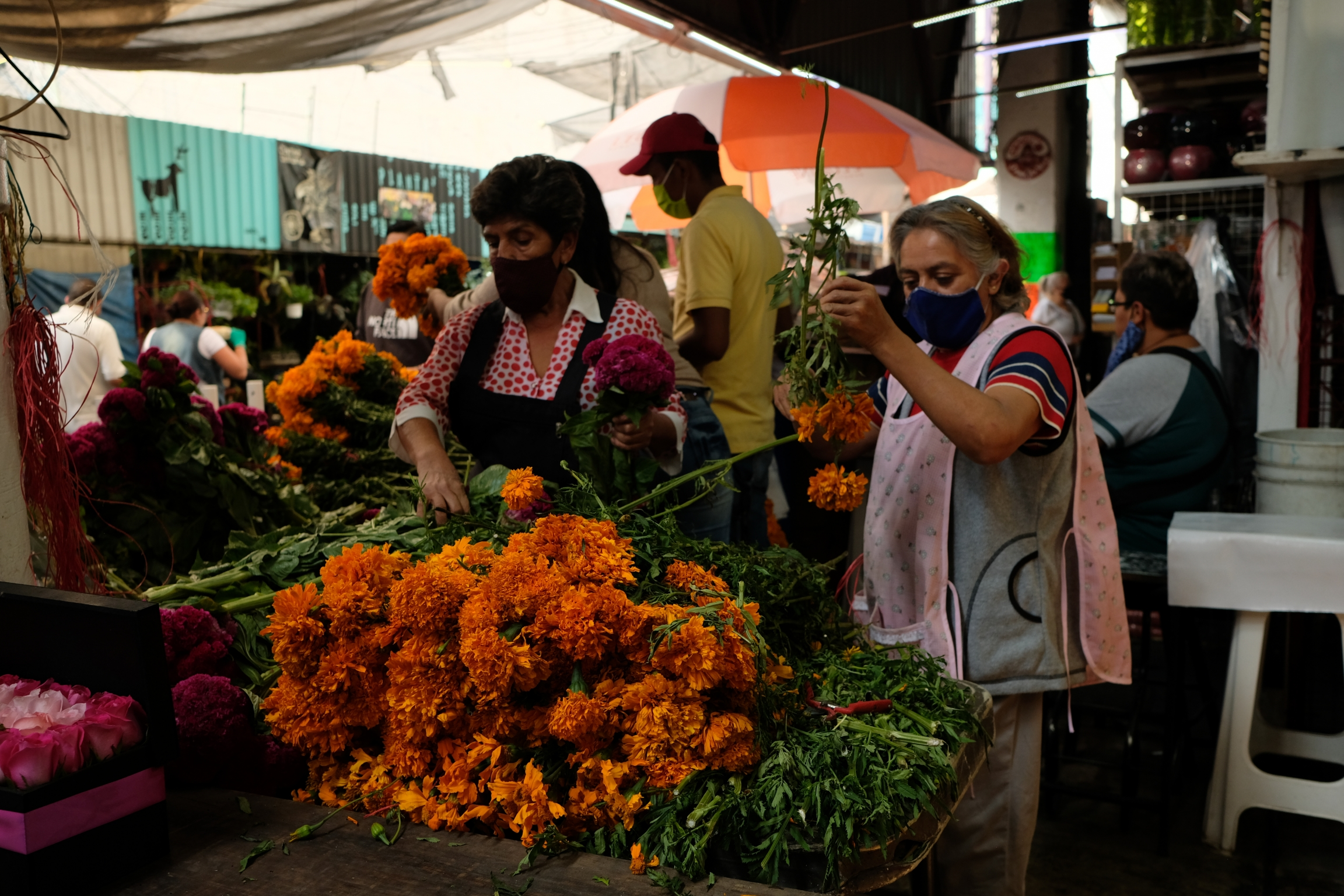 Flower vendors prep freshly harvested marigolds to sell. Many vendors agree that this year sales are very slow.