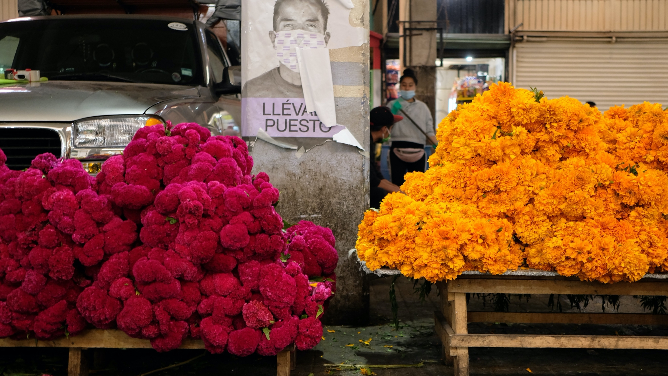 A public service announcement encouraging face masks is flanked by marigolds and terciopelo flowers at Mercado de Jamaica.