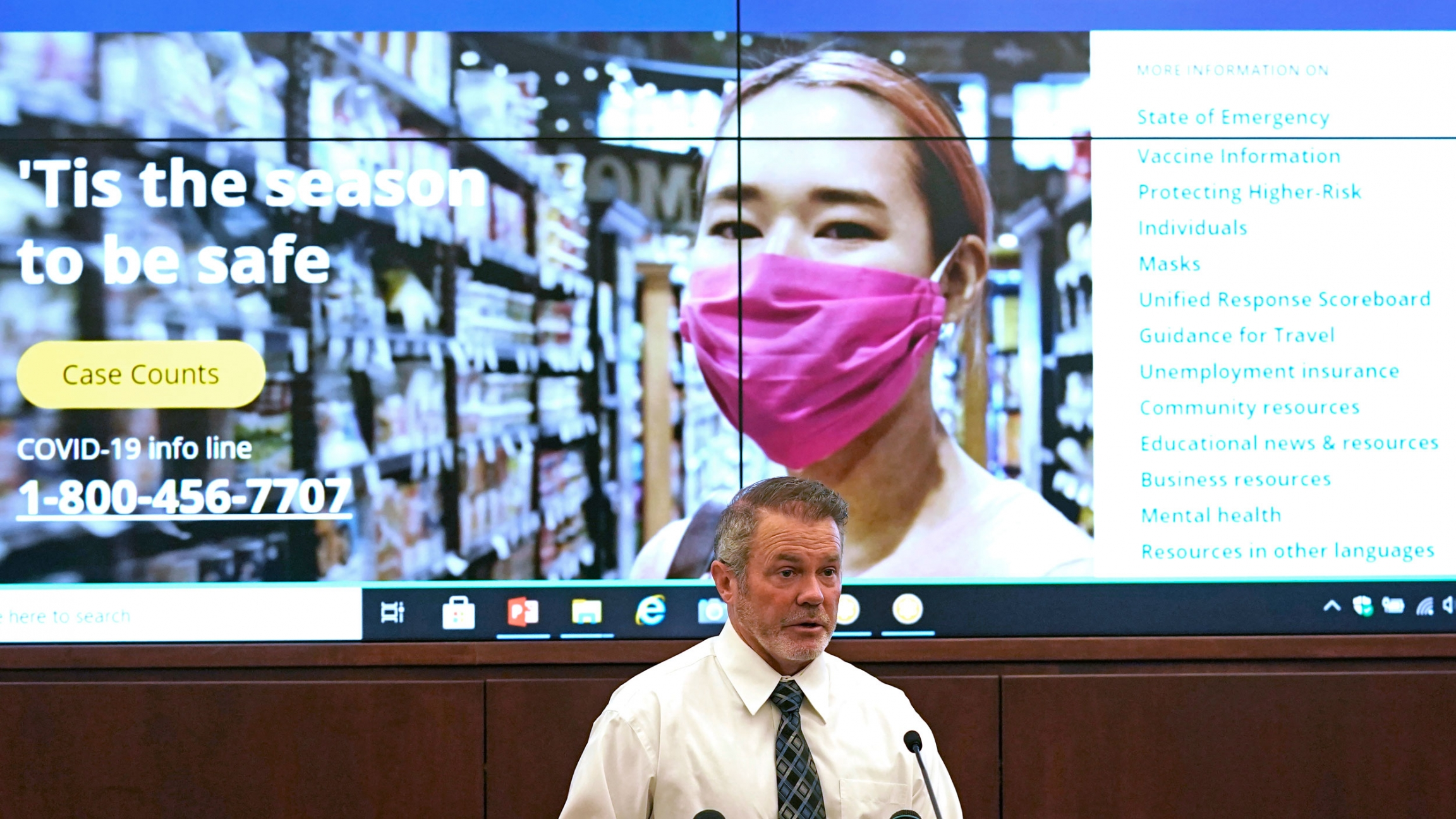 A man wearing a white shirt and gray tie is shown speaking a t podium with a screen behind him showing promotional material on coronavirus safety.