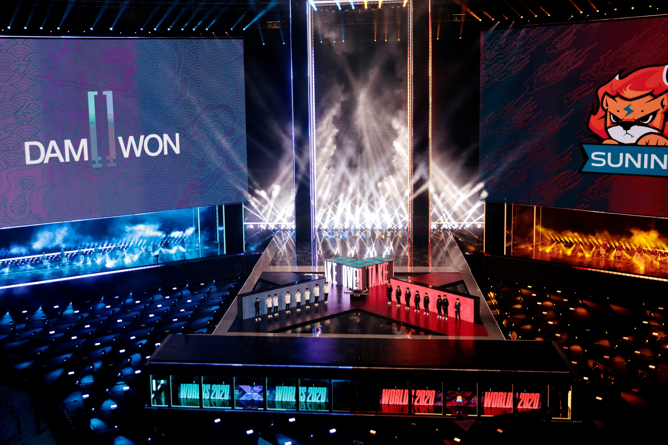 A huge stadium with blue, white and red lights features competitive esports players on stage.