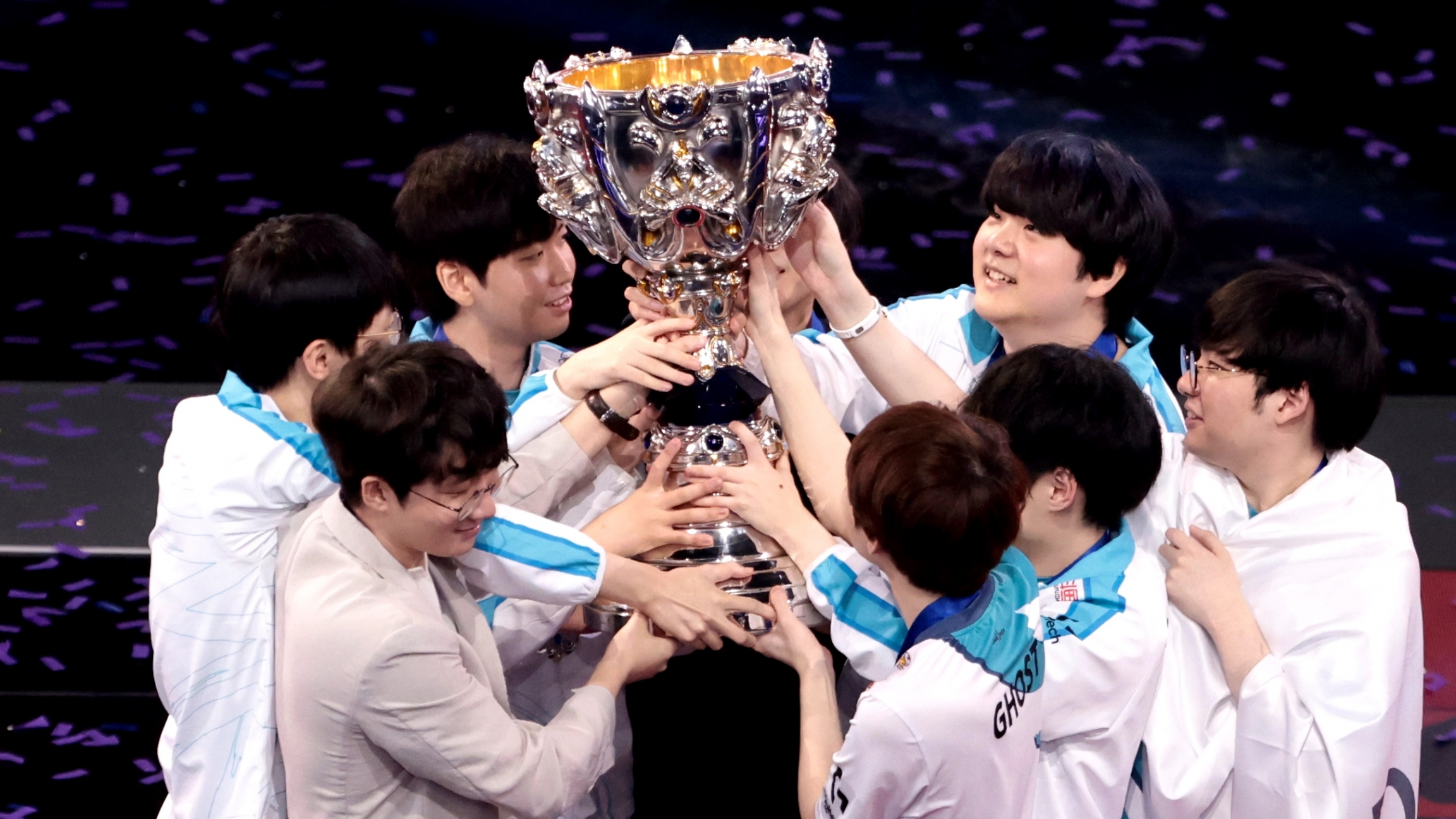 A group of Korean young men huddle around and hold up a trophy.