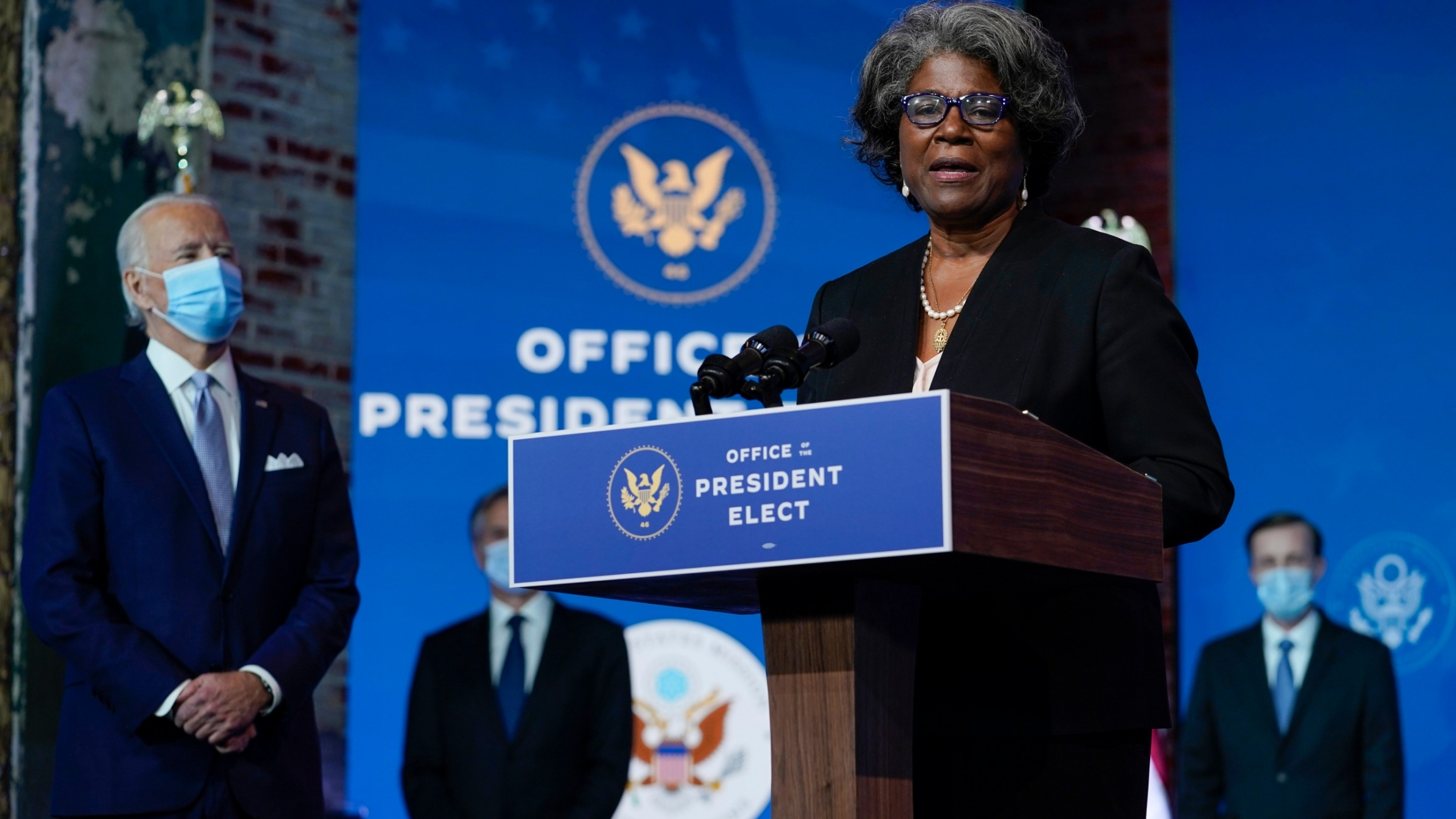 Joe Biden, a white man, is stands near nominee Linda Thomas-Greenfield, a Black woman, who is wearing a dark blue suit onstage at a podium.