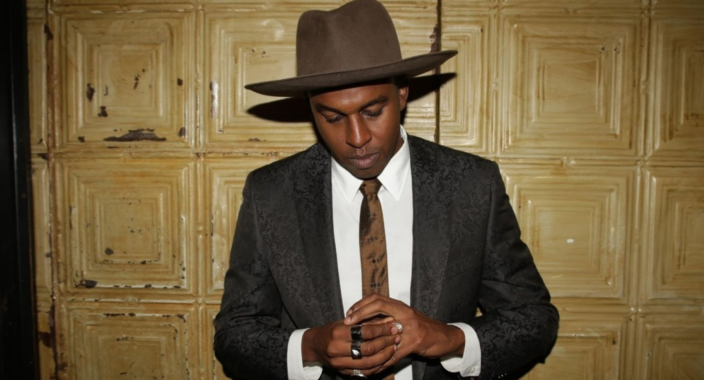 Sinkane is shown wearing a suit and wide-brimmed hat.